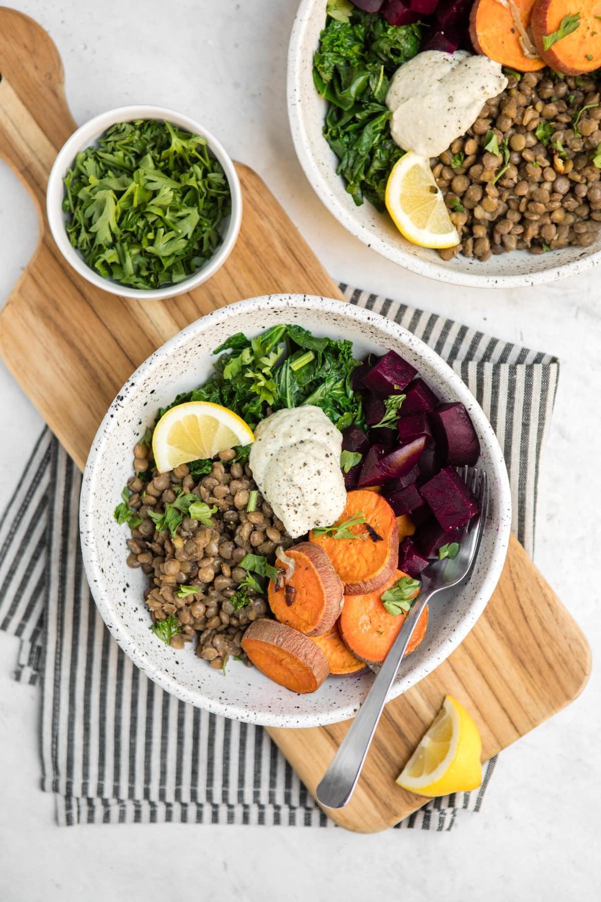 white bowls of warm lentil salad with roasted vegetables on black striped towel