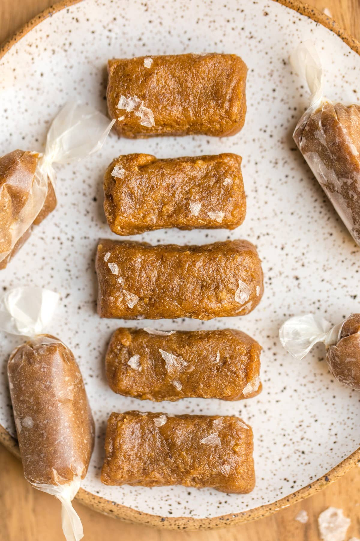 healthy salted caramel bites in row on white speckled plate