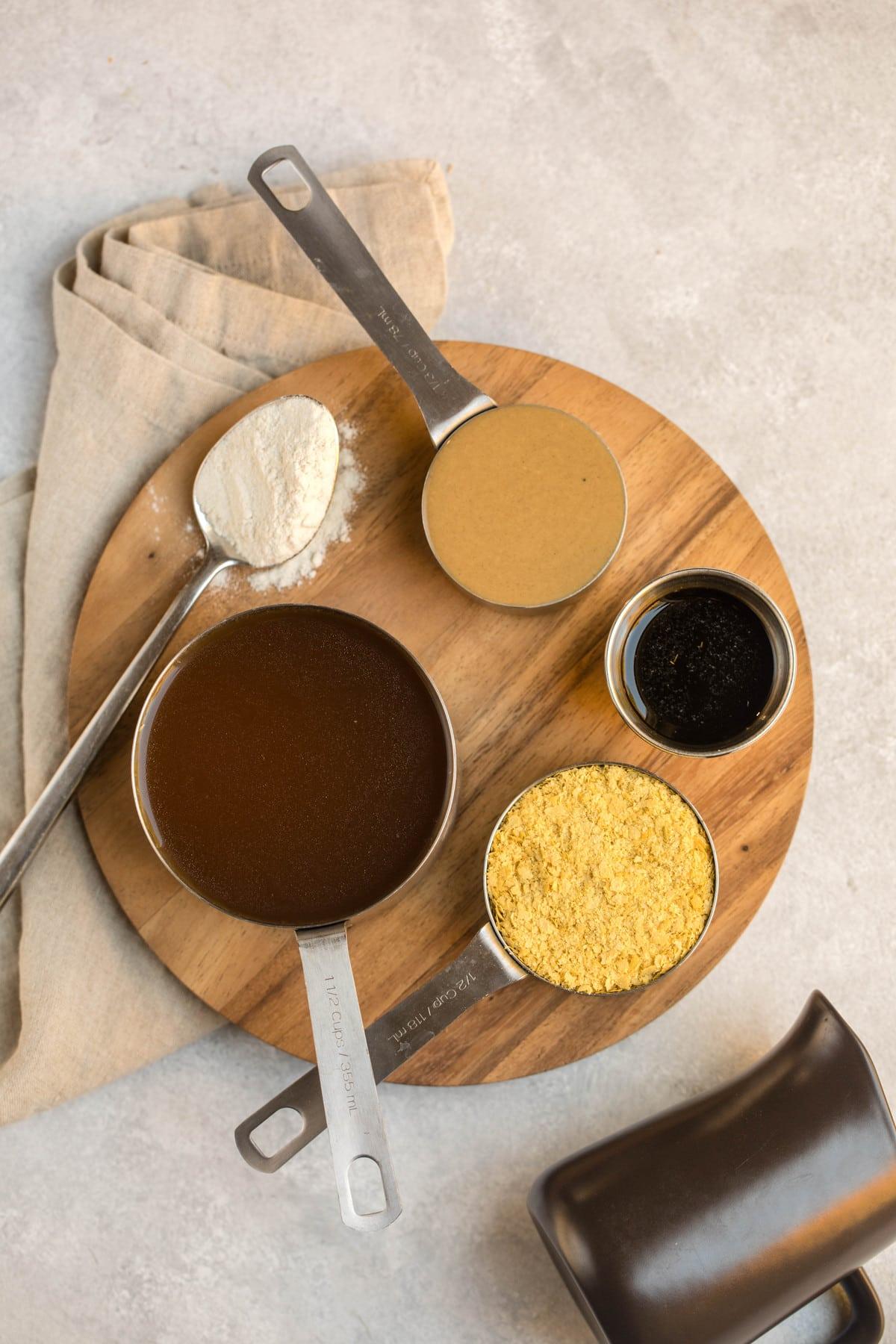 ingredients for vegan tahini gravy on round wood cutting board