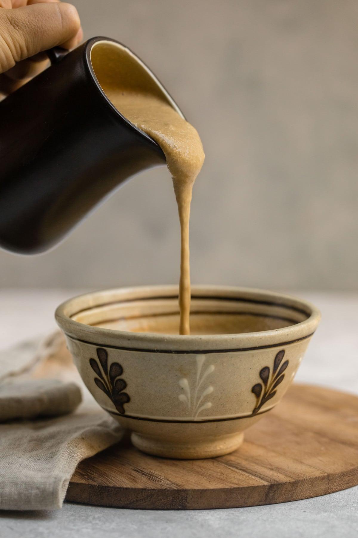 brown gravy pitcher pouring tahini gravy into tan bowl