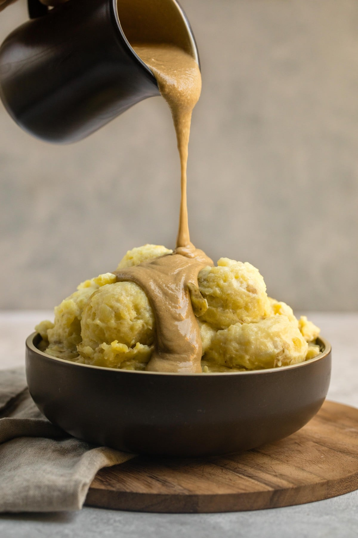 dark brown bowl of mashed potatoes with tahini gravy being poured over the top