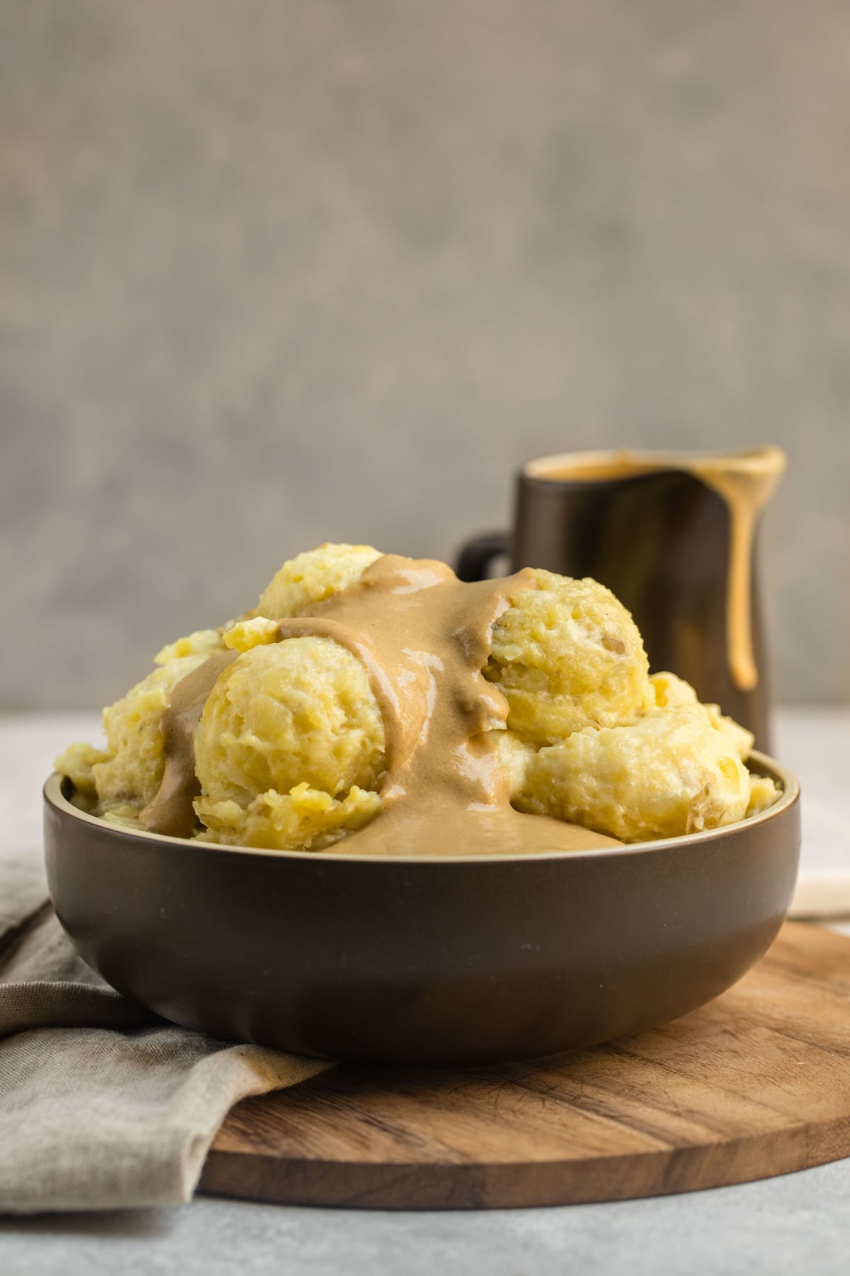 brown bowl filled with mashed potatoes and topped with tahini gravy