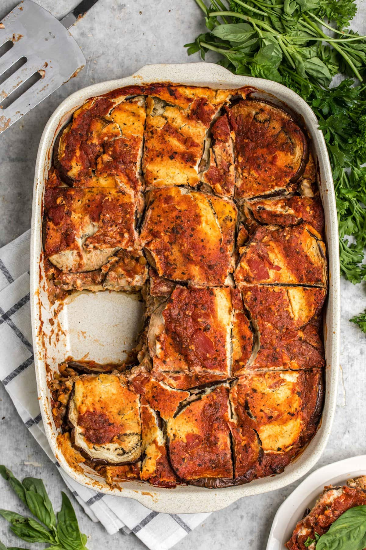 large white casserole dish of baked eggplant lasagna with one slice taken out