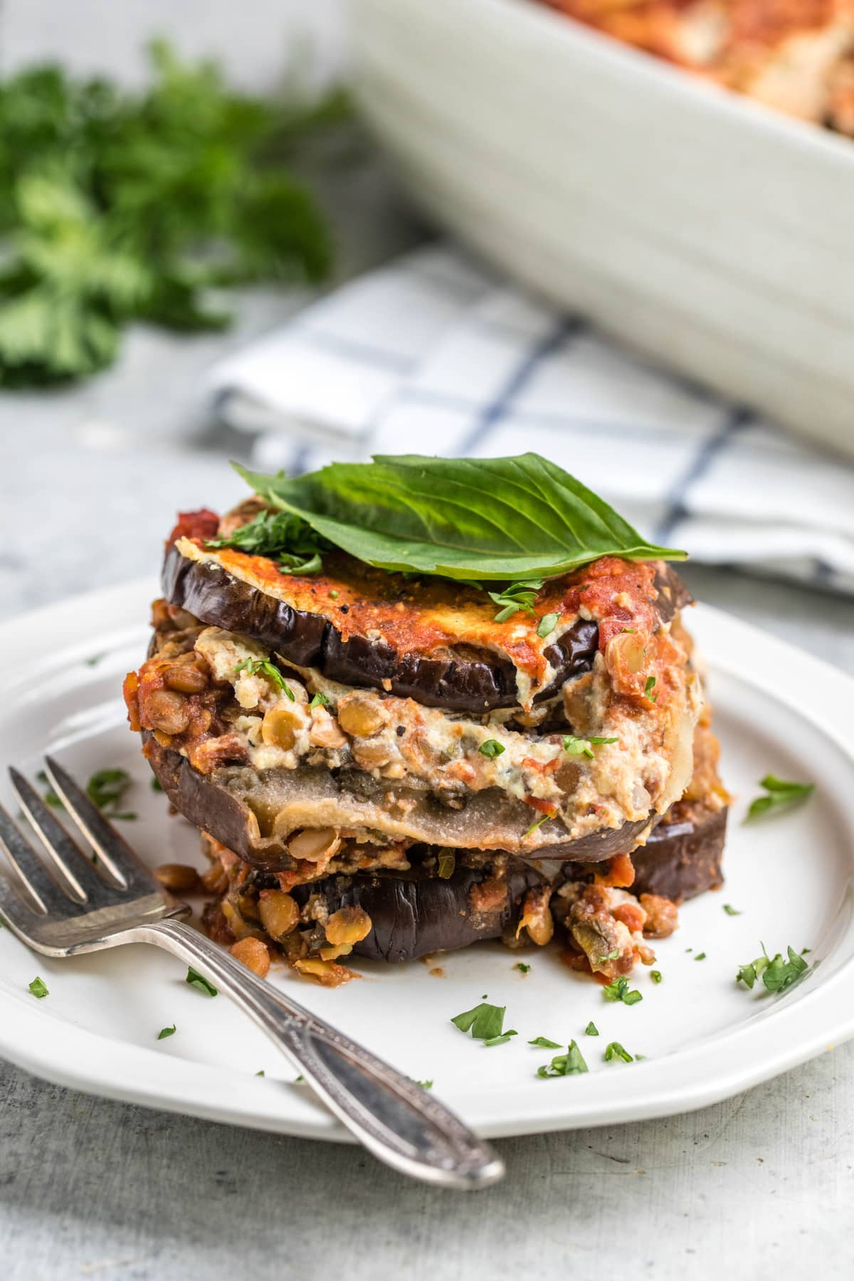 cross photo of layers of eggplant lasagna on small white plate topped with fresh basil leaf