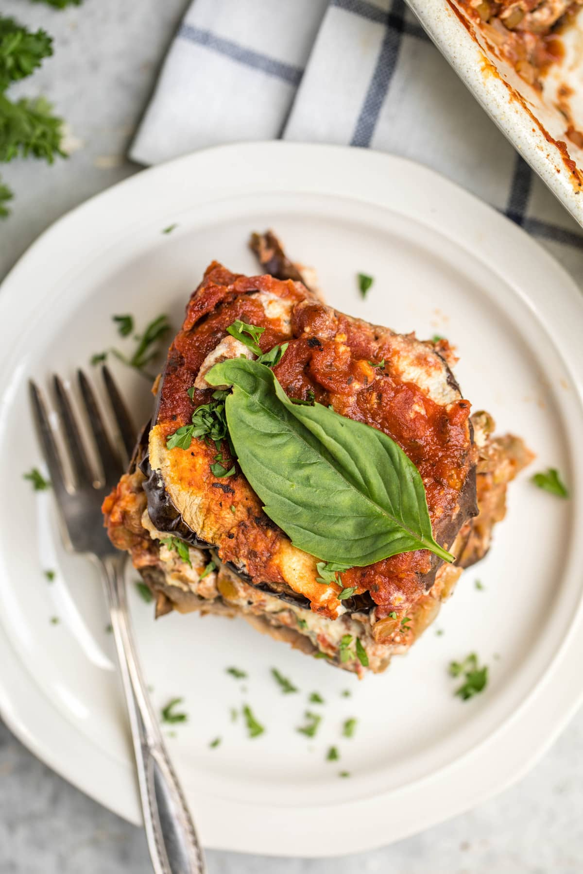 overhead shot of vegan eggplant lasagna topped with fresh basil leaf on small white plate