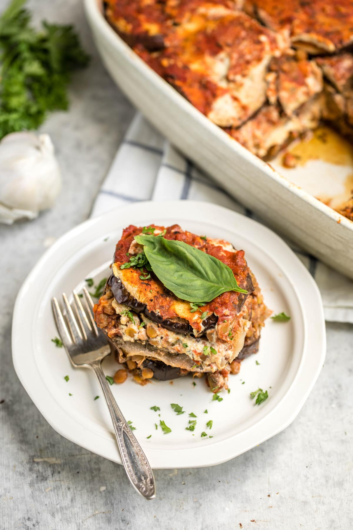 slice of vegan eggplant lasagna on small white plate with larger casserole dish in the background
