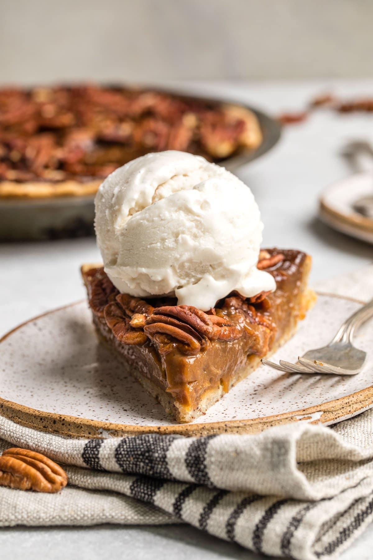vegan pecan pie topped with vanilla ice cream scoop on white plate