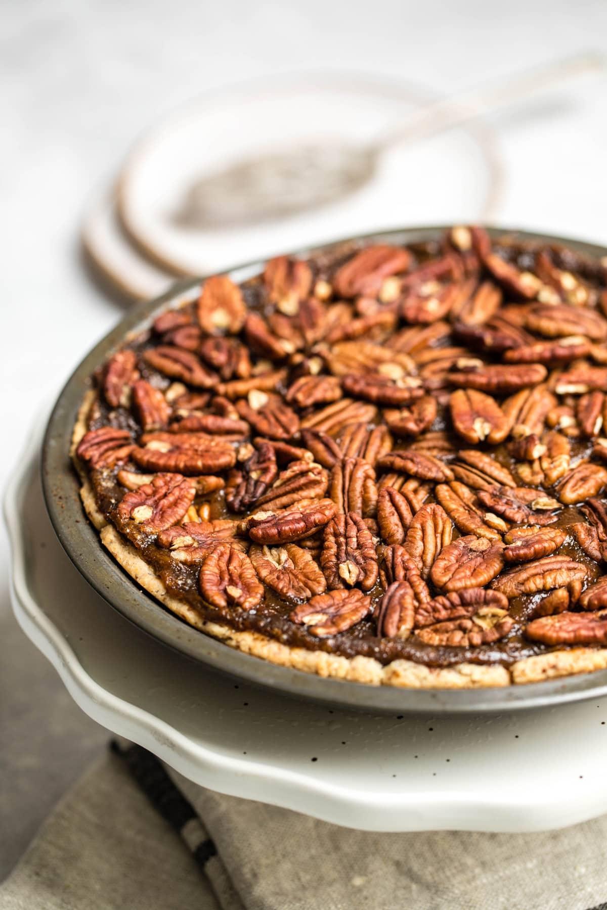 vegan pecan pie in pie tin on white pie serving plater on marble background