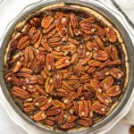 vegan pecan pie in silver pie tin on white marble background surrounded by pecan pieces