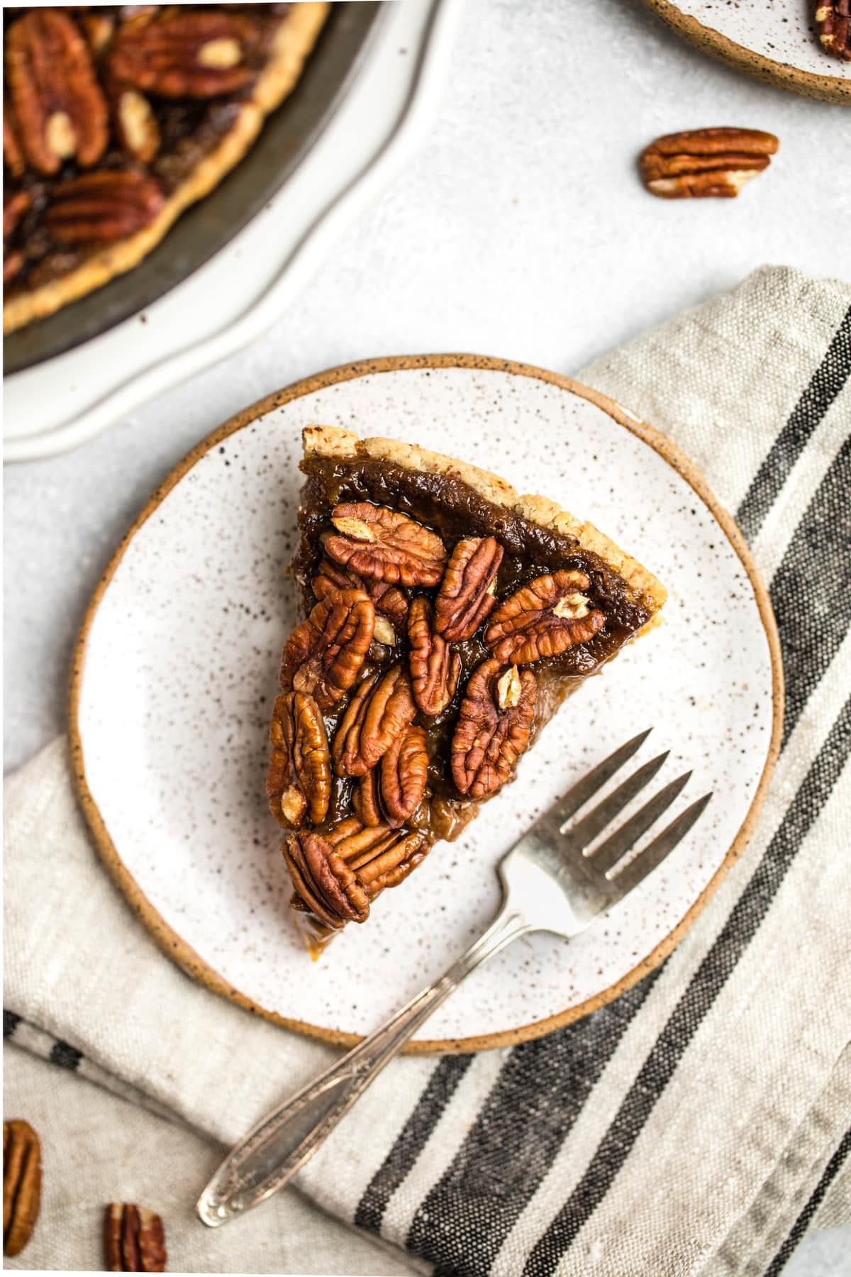slice of pecan pie on white speckled plate on grey tea towel and marble bacground