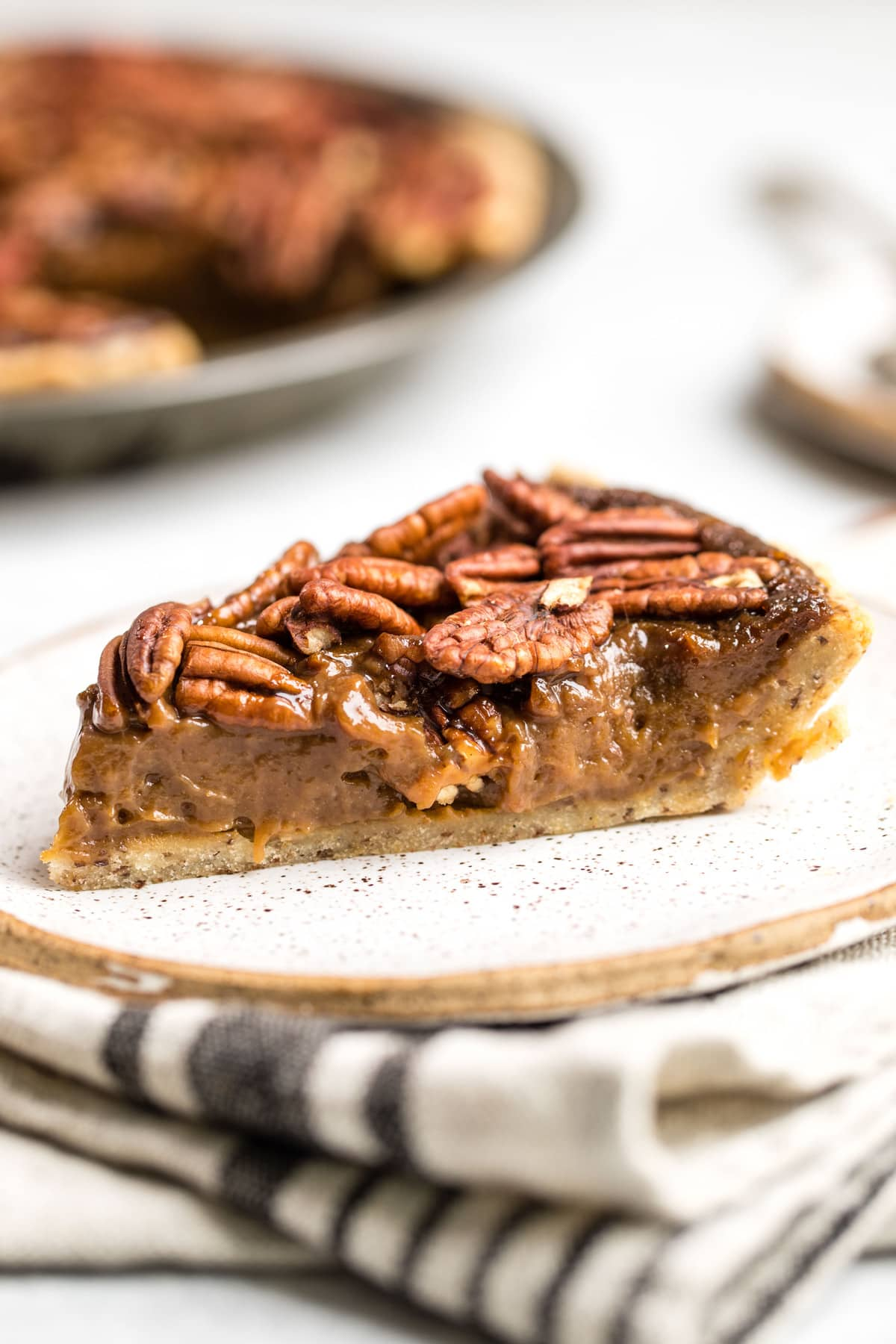 side slice of pecan pie with layers of filling, pecans, and pie crust on white plate