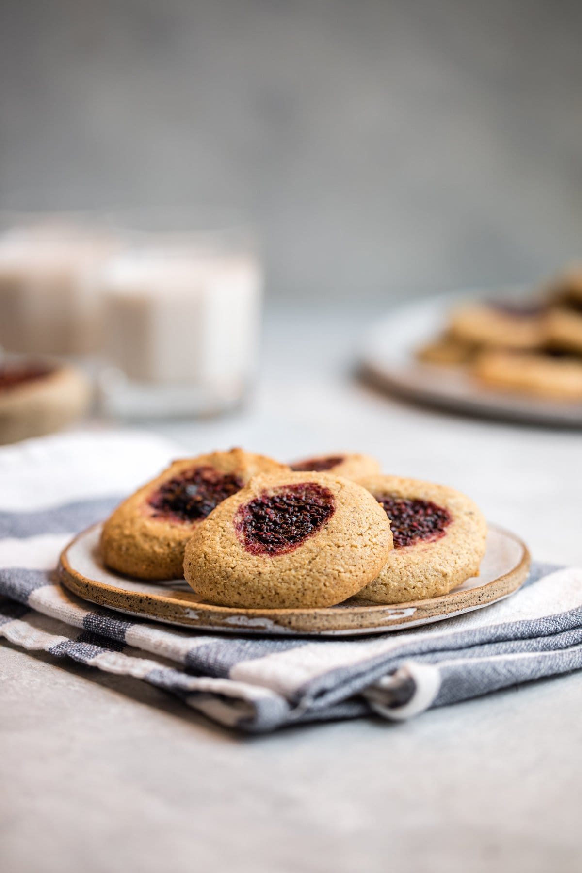 small white plate filled with almond flour thumbprint cookies