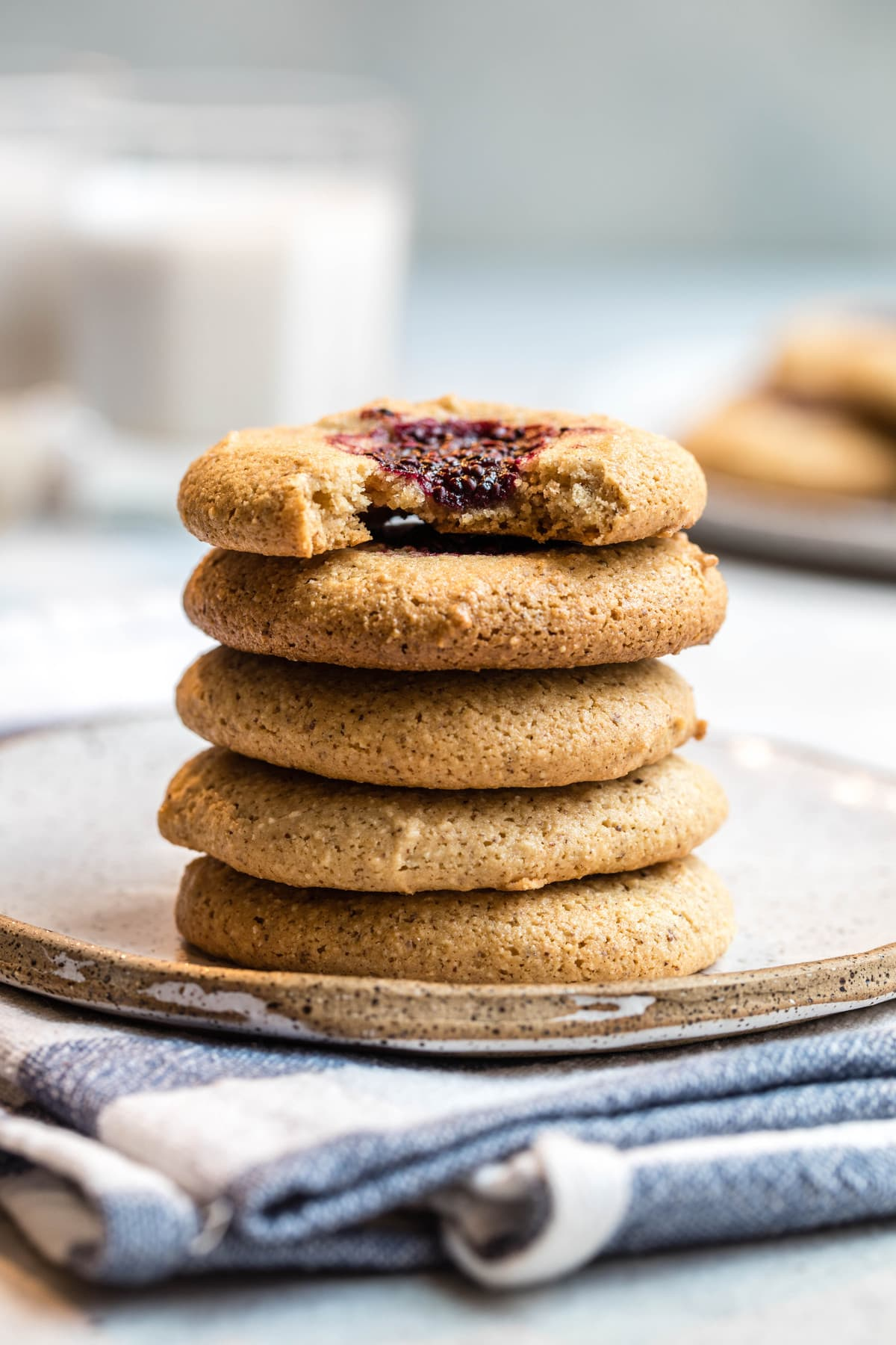 stack of almond flour cookies on white speckled plate with bite taken out of top cookie