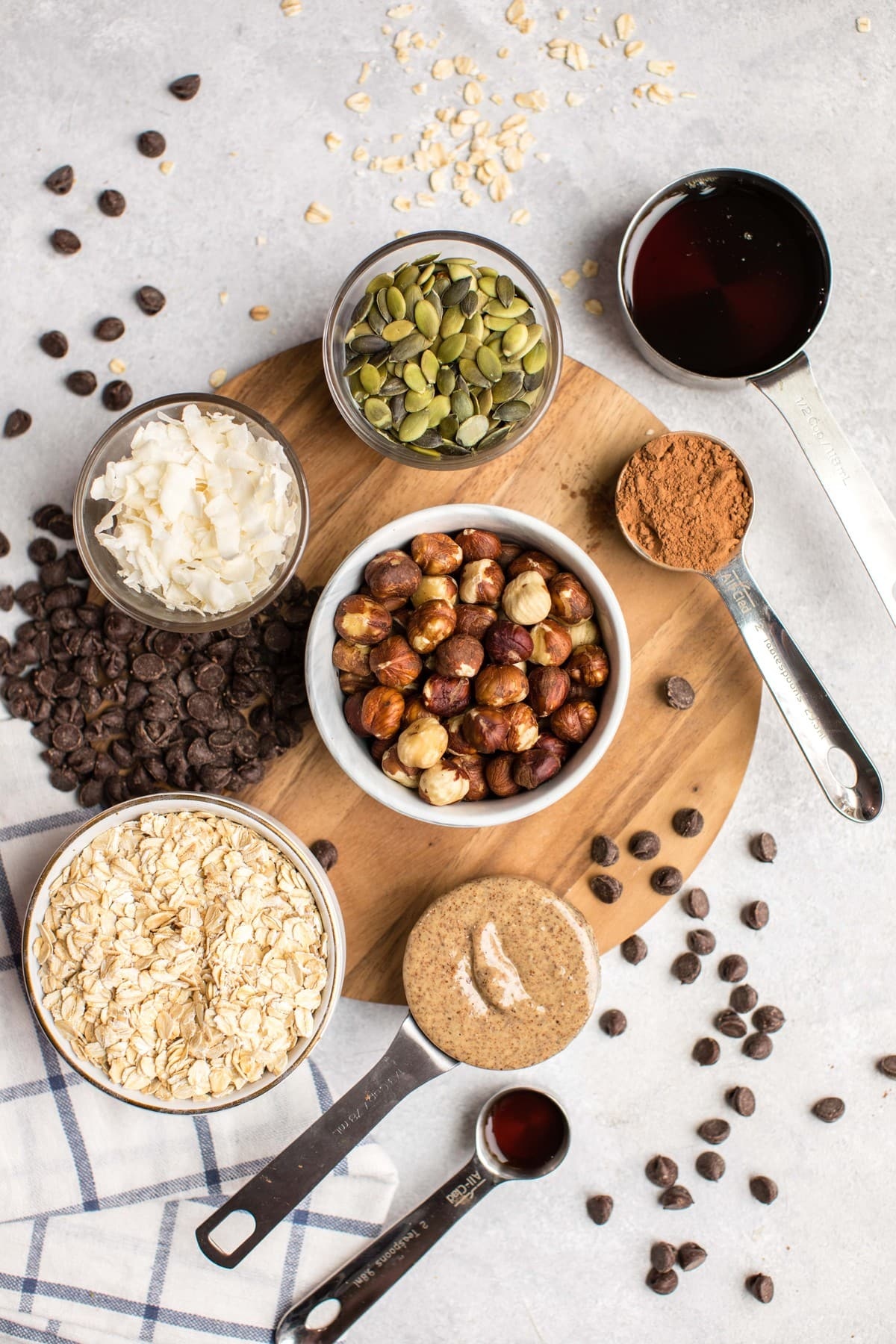 ingredients for chocolate hazelnut granola in small cups and bowls on round wooden cutting board with striped blue and white towel