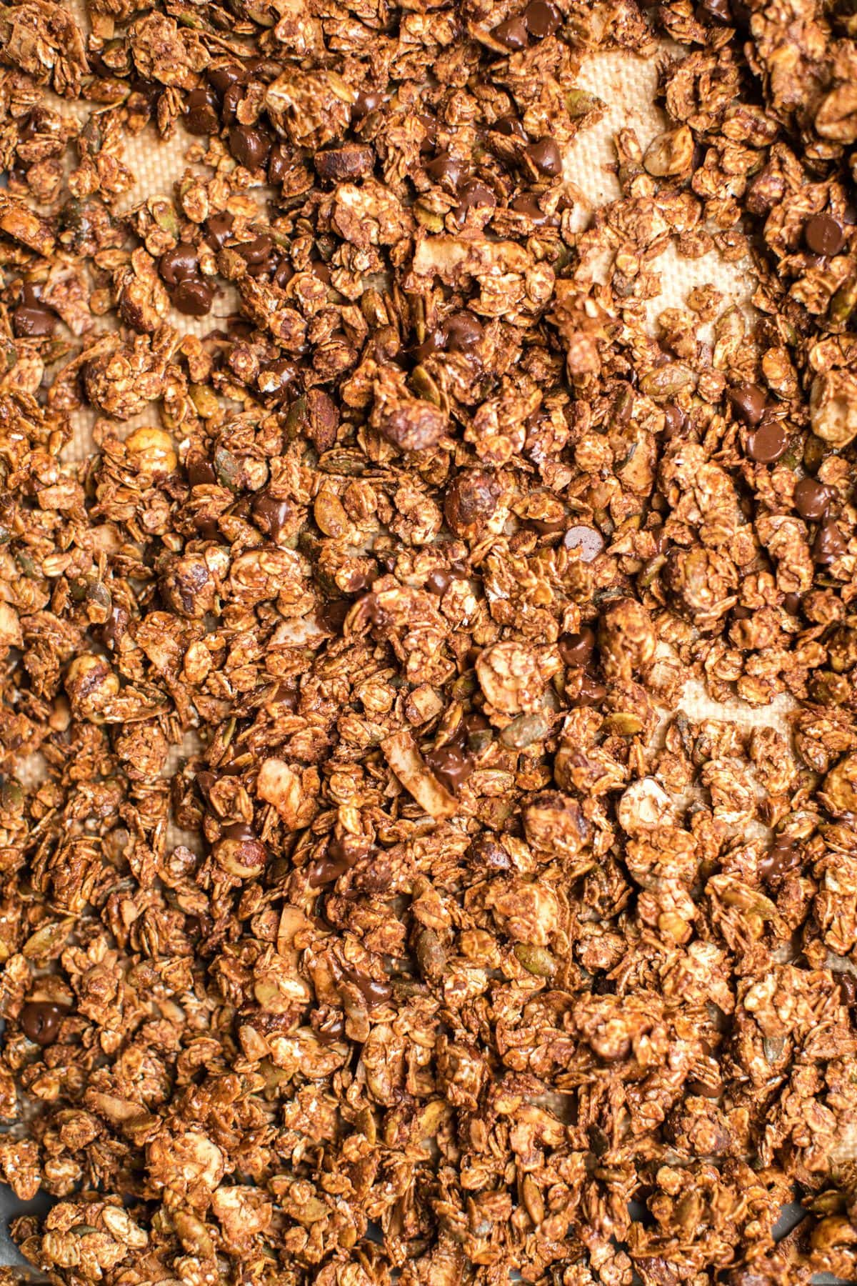 baked chocolate hazelnut granola spread out on baking tray lined with silicone mat