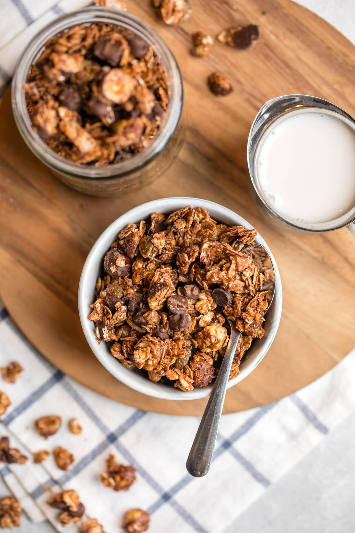 small white bowl filled with chocolate hazelnut granola on round wood cutting board