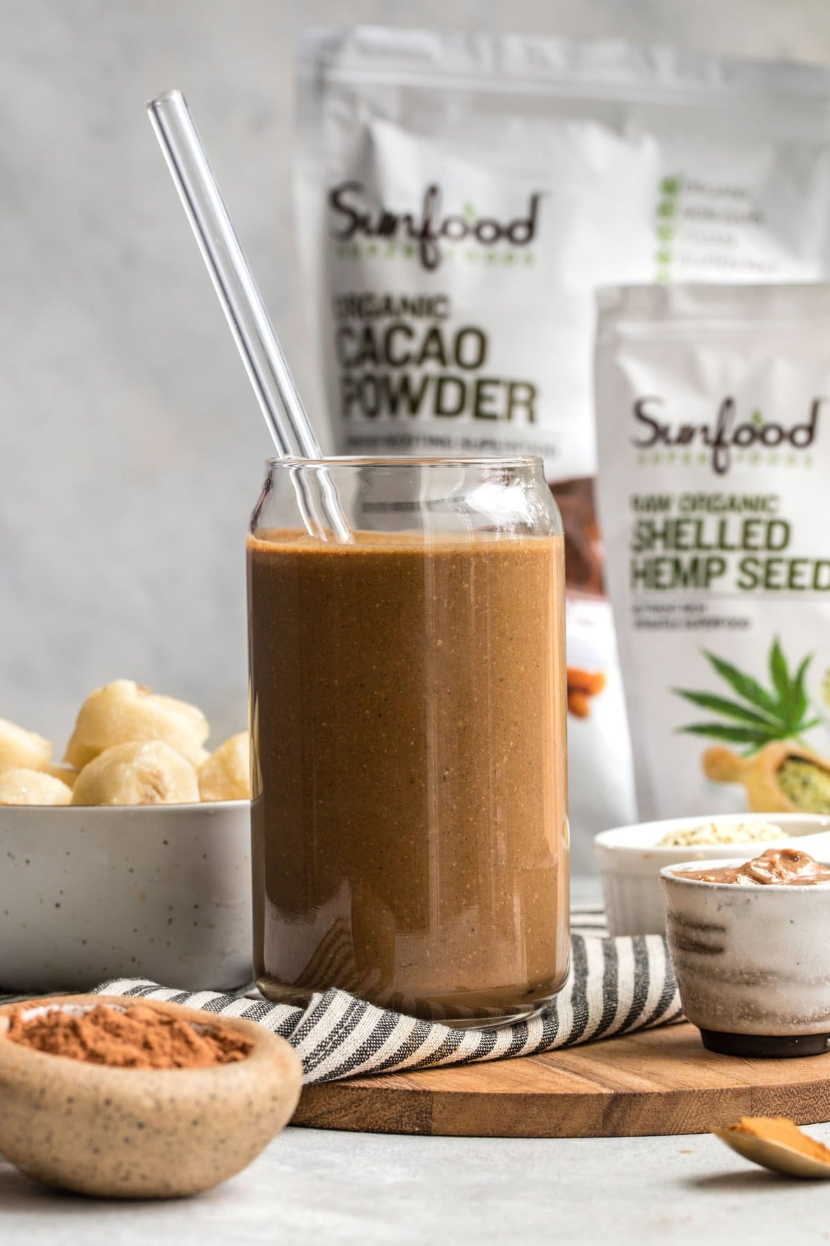 chocolate hemp smoothie in glass with straw with sunfood product in background