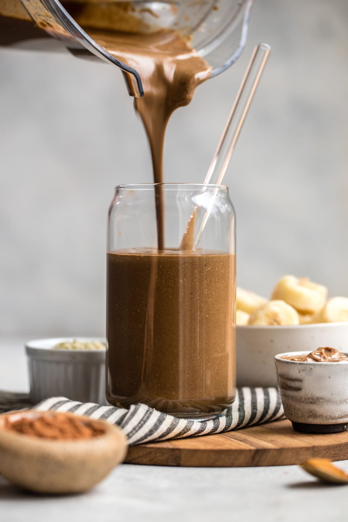 blender pouting chocolate hemp smoothie into tall glass with straw