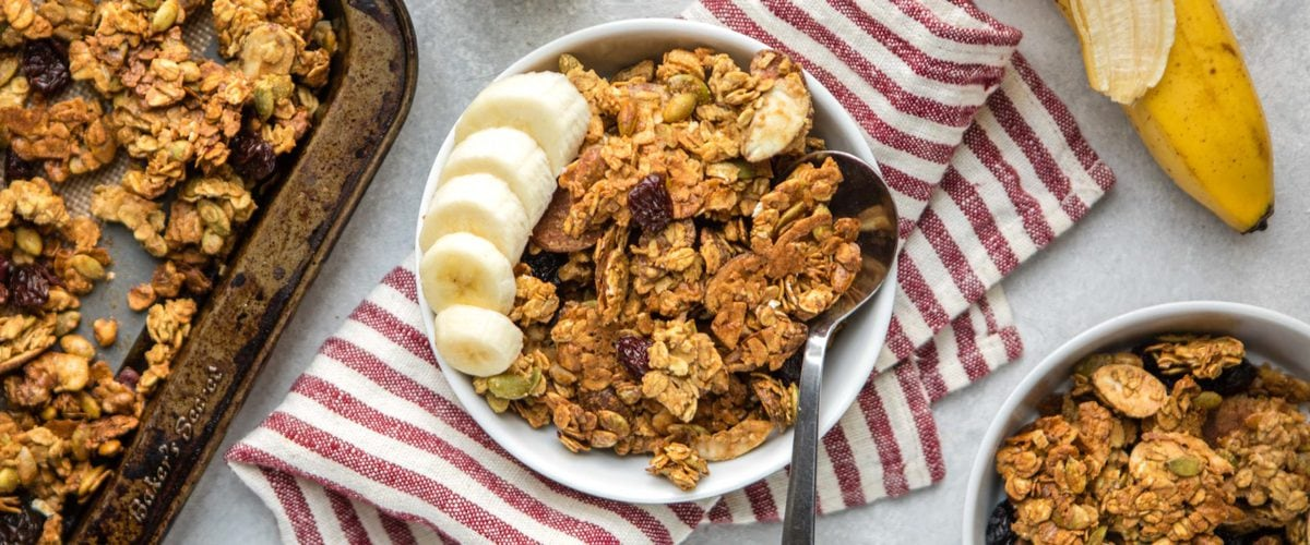 close up photo of white bowl of easy vegan granola clusters with serving spoon and almond milk