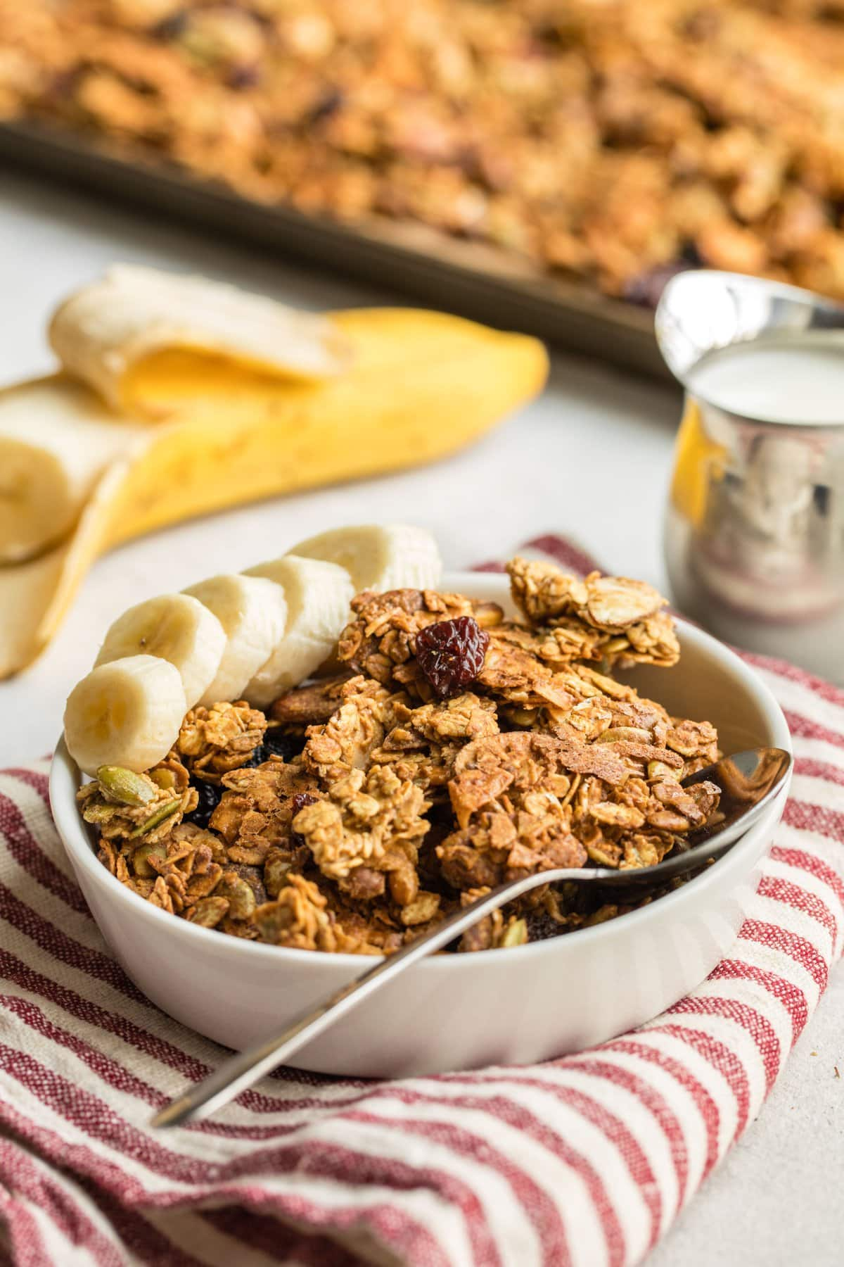 angled shot of white bowl filled with granola with sliced banana on the side on red striped napkin