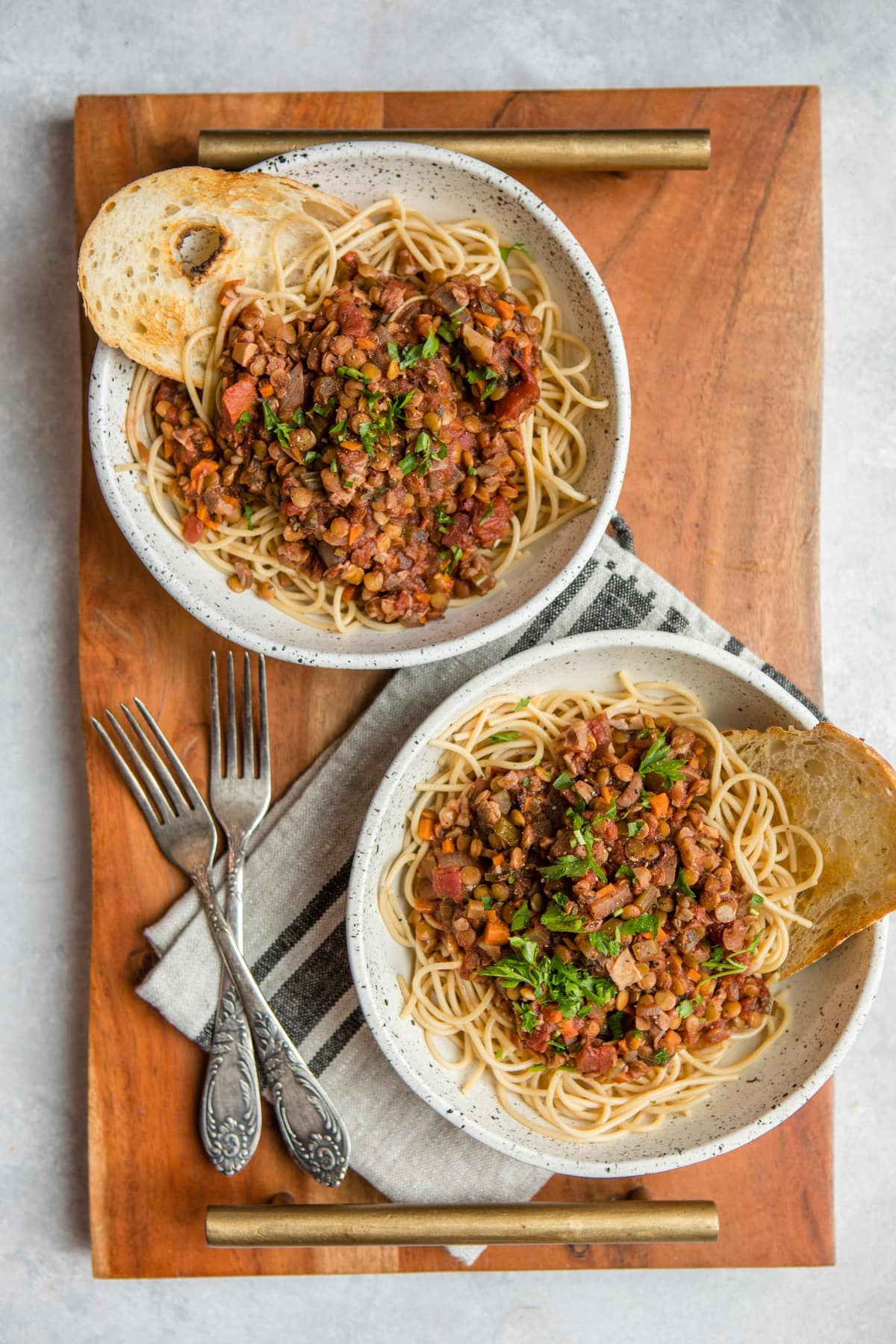 two bowls of lentil bolognese over pasta with toasted bread on white cutting board