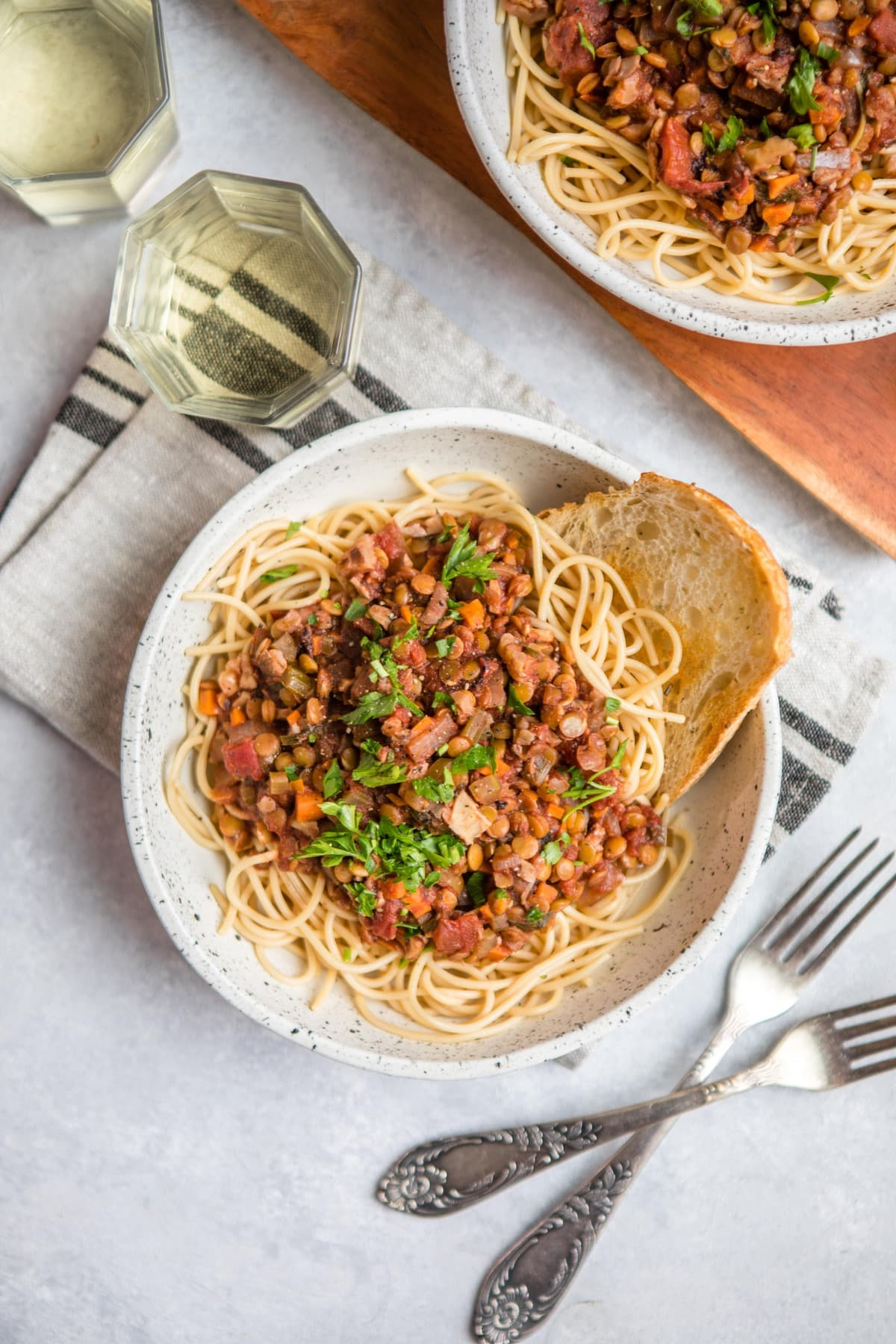 white bowl of cooked pasta topped with lentil bolognese and a glass of white wine