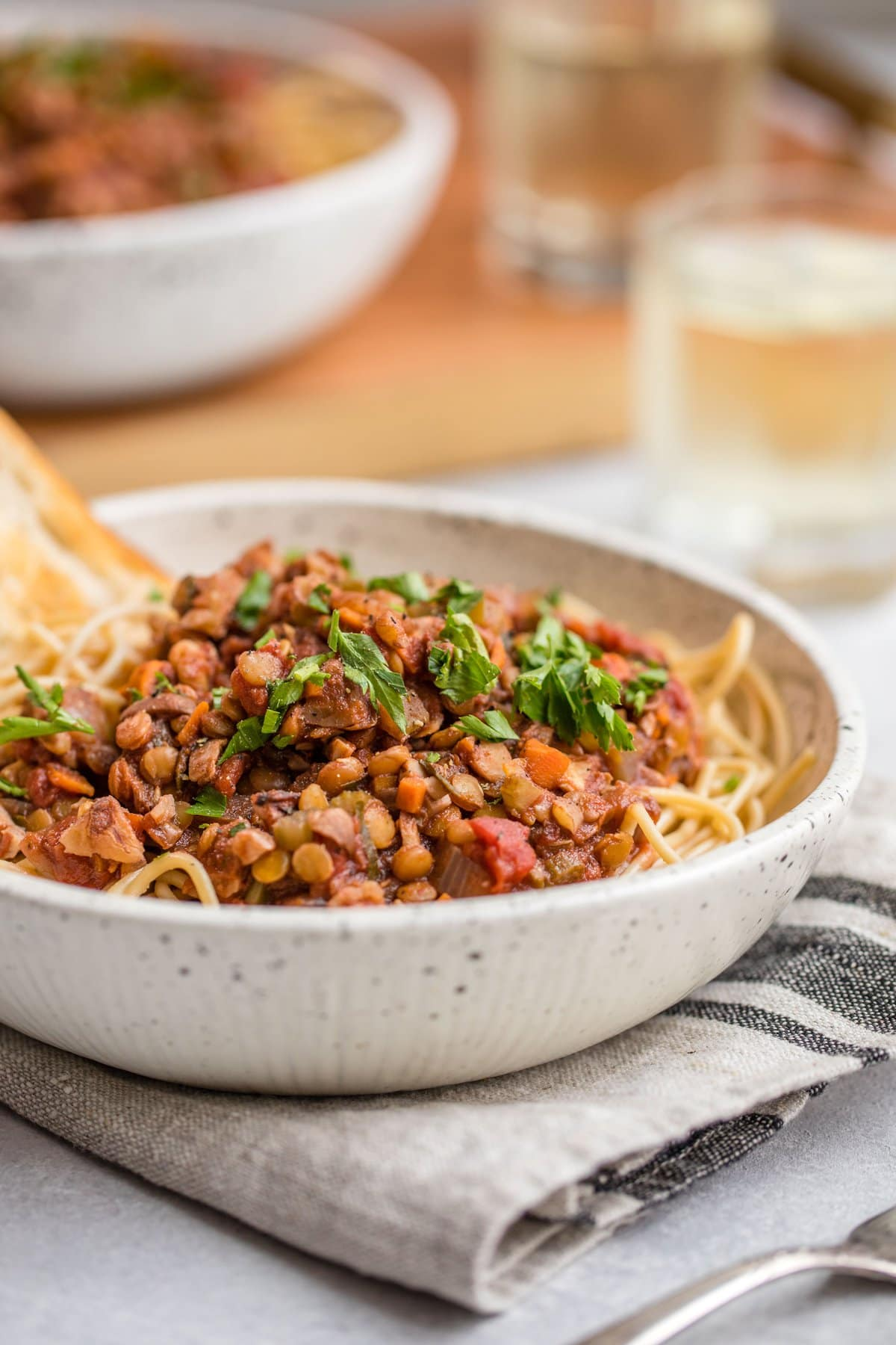 close up photo of Lentil Bolognese sauce over cooked pasta in white bowl topped with fresh parsley