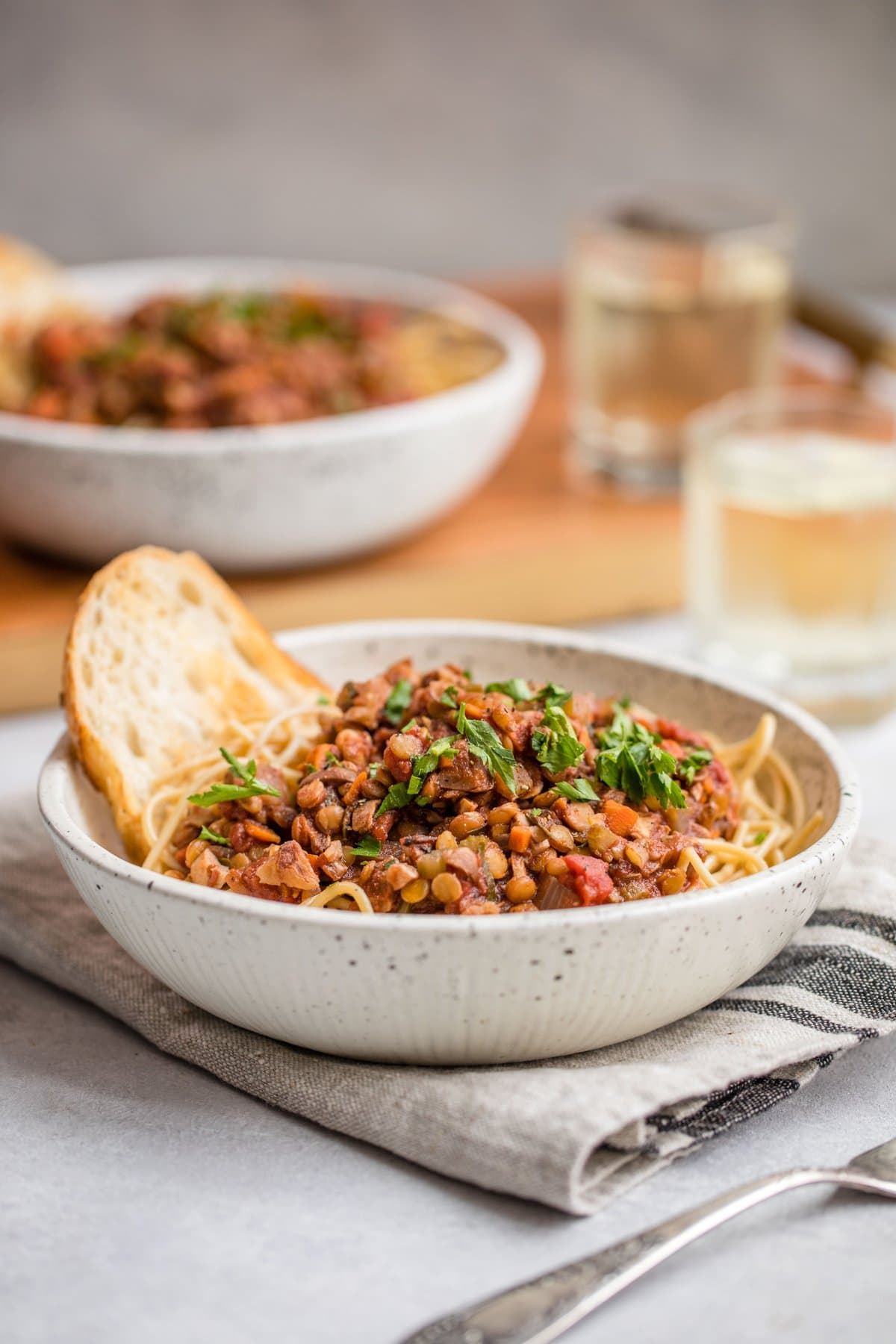 lentil bolognese topped with fresh parsley and garlic bread in speckled white bowl