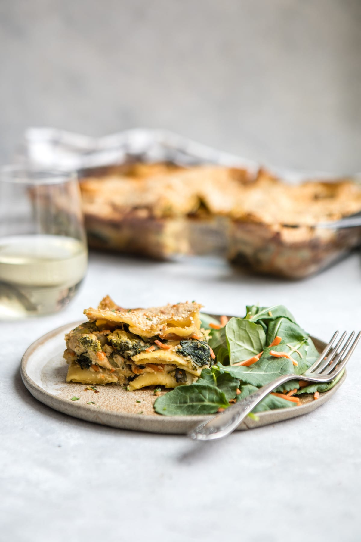 picece of lasagna on tan plate with salad on white background