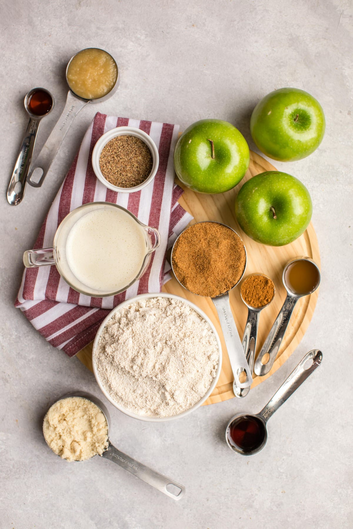 ingredients for apple cinnamon muffins on round wood cutting board with red striped napkin