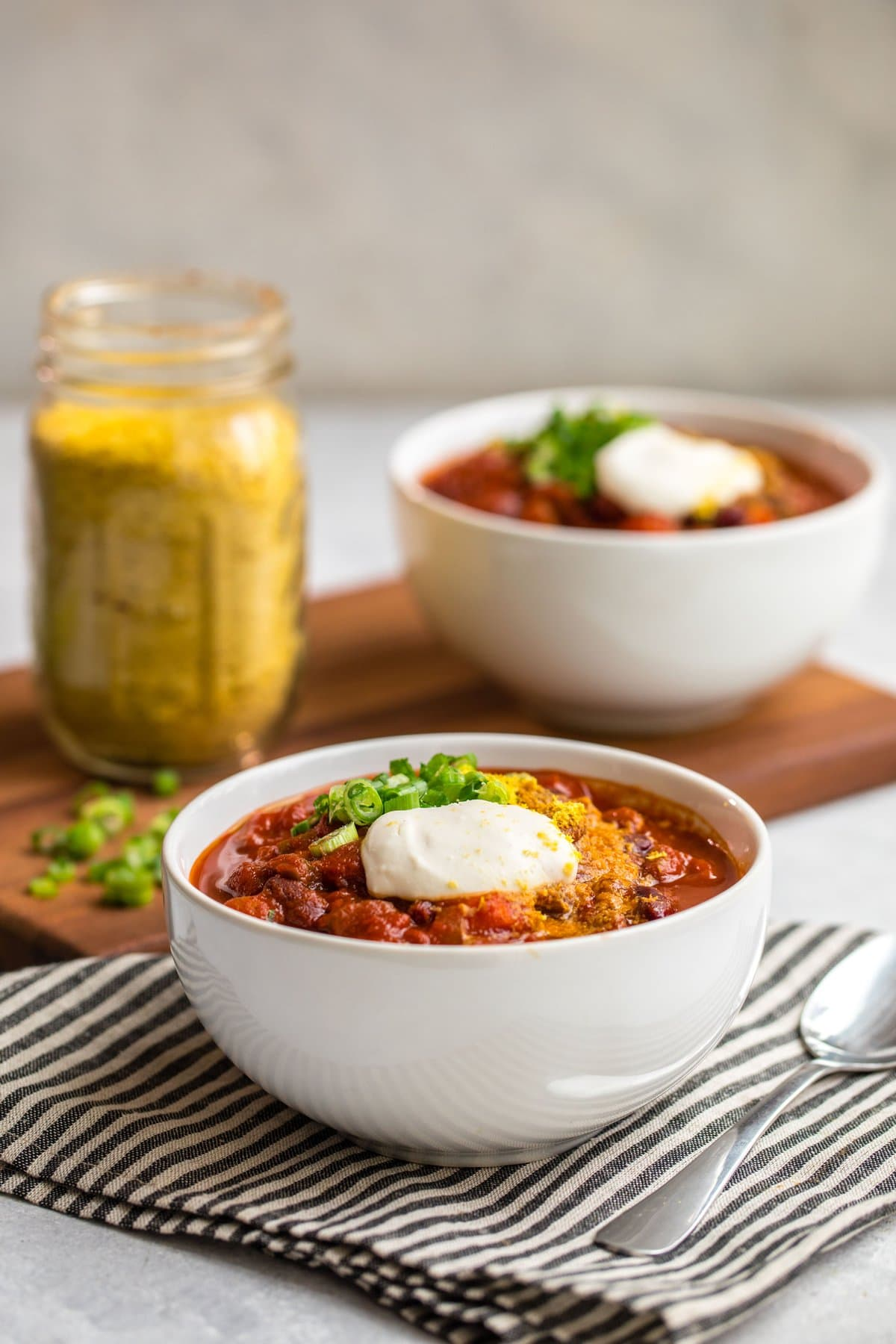 side shot of two bowls of vegan chili on wood cutting board