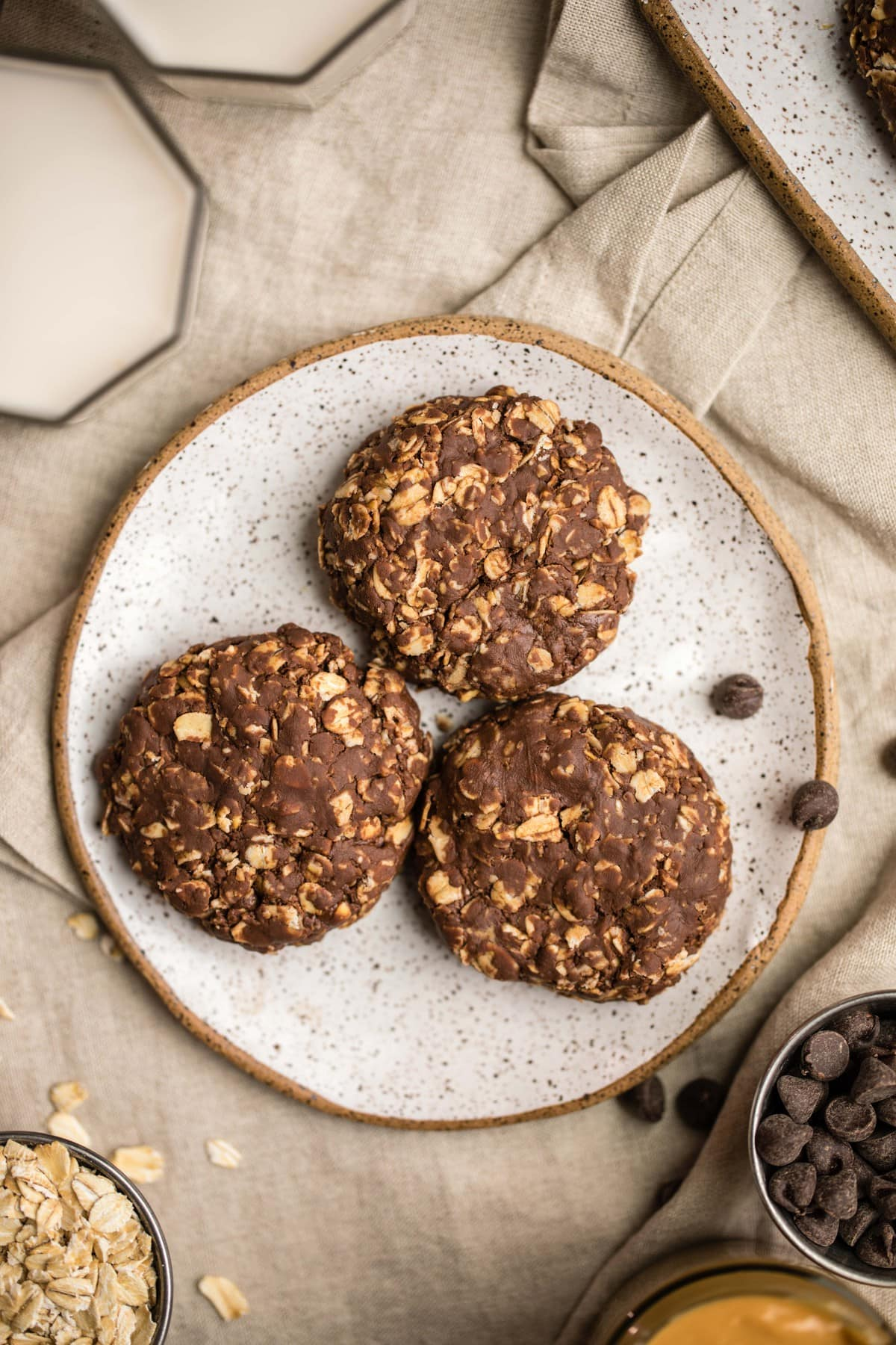 3 chocolate peanut butter cookies on white speckled plate with glass of milk