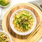 white speckled bowl of sesame noodles topped with cucumber, green onions, and chili oil