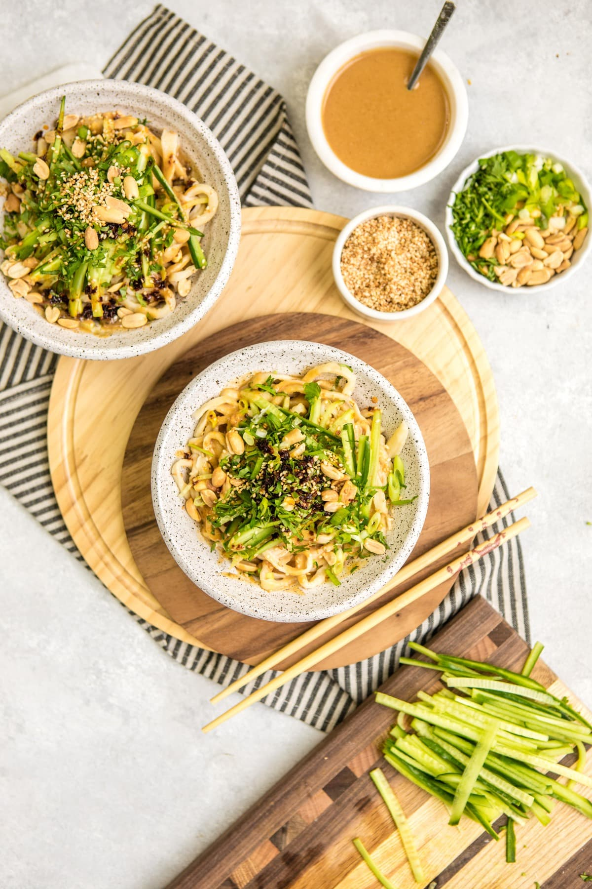 two white bowls of cooked sesame noodles topped with cucumber, green onion, chili oil, and peanuts