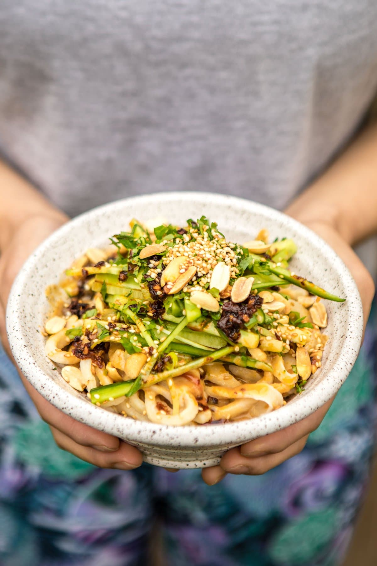 white speckled bowl of sesame noodles topped with green onion, peanuts, and chili oil