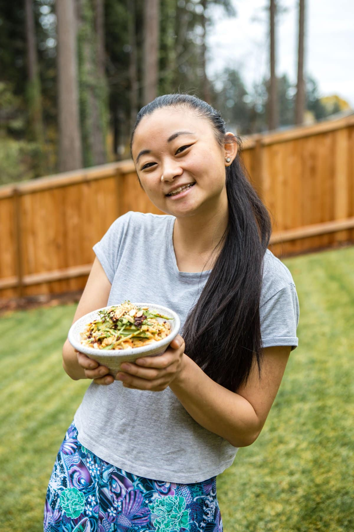 liz smiling and holding bowl of sesame noodles