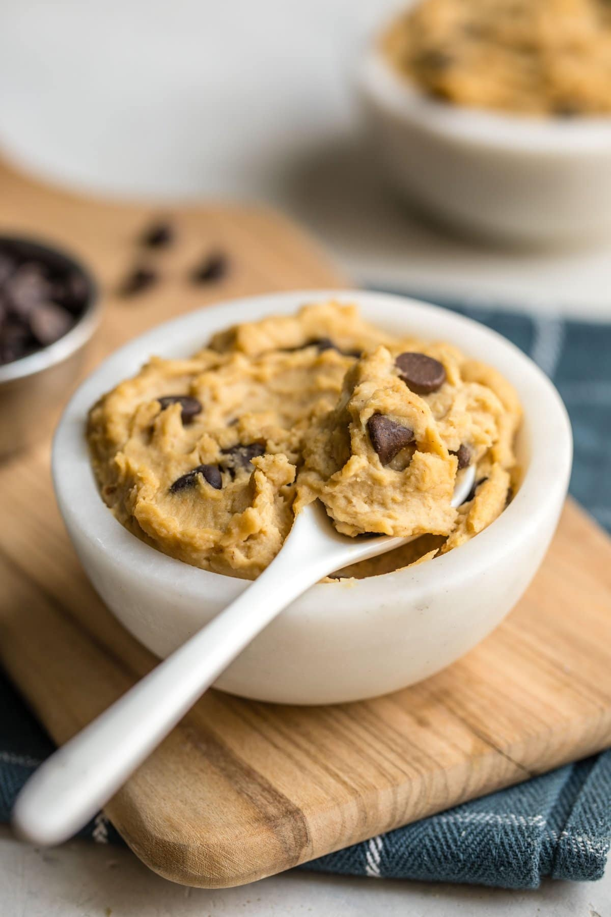 white bowl of chocolate chip cookie dough on wood serving tray with teal tea towel
