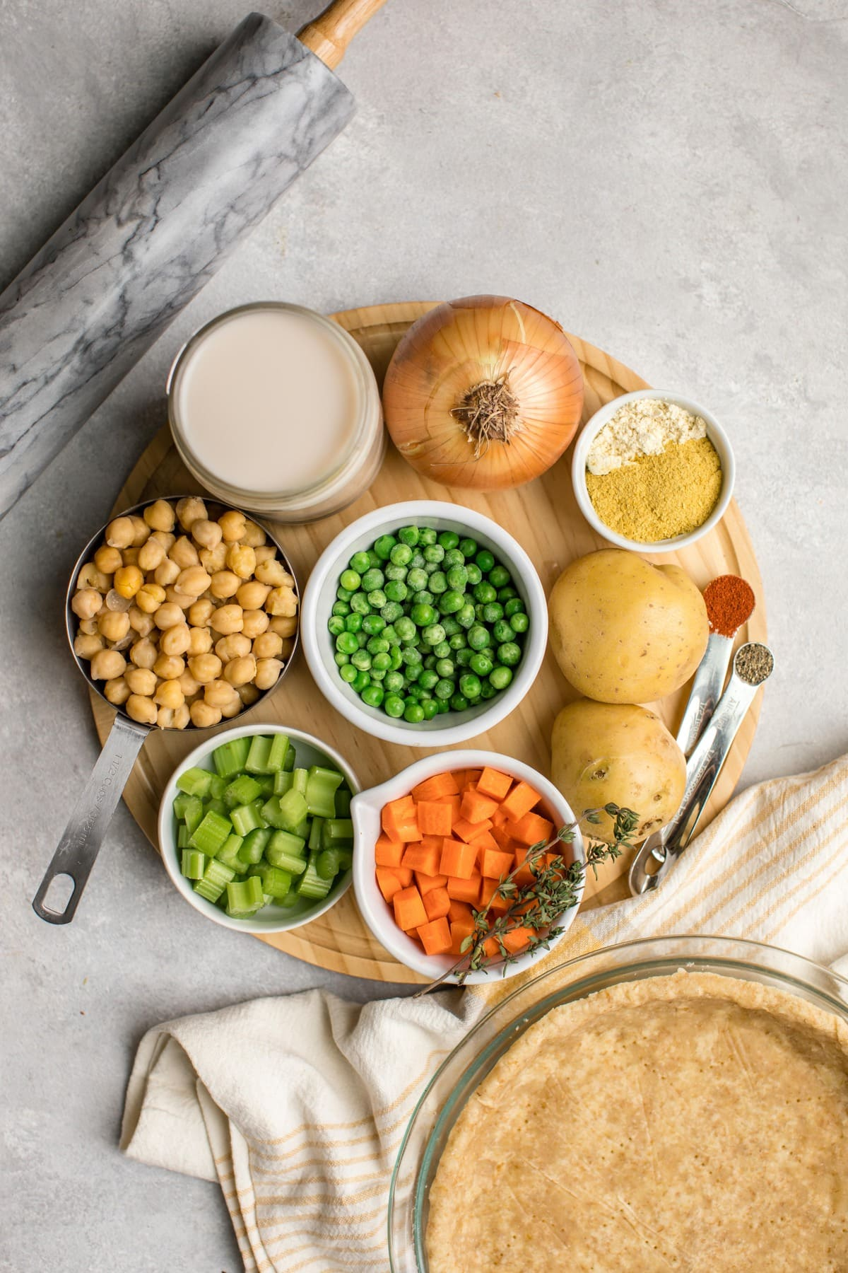 ingredients for chickpea pot pie arranged on circular wood cutting board