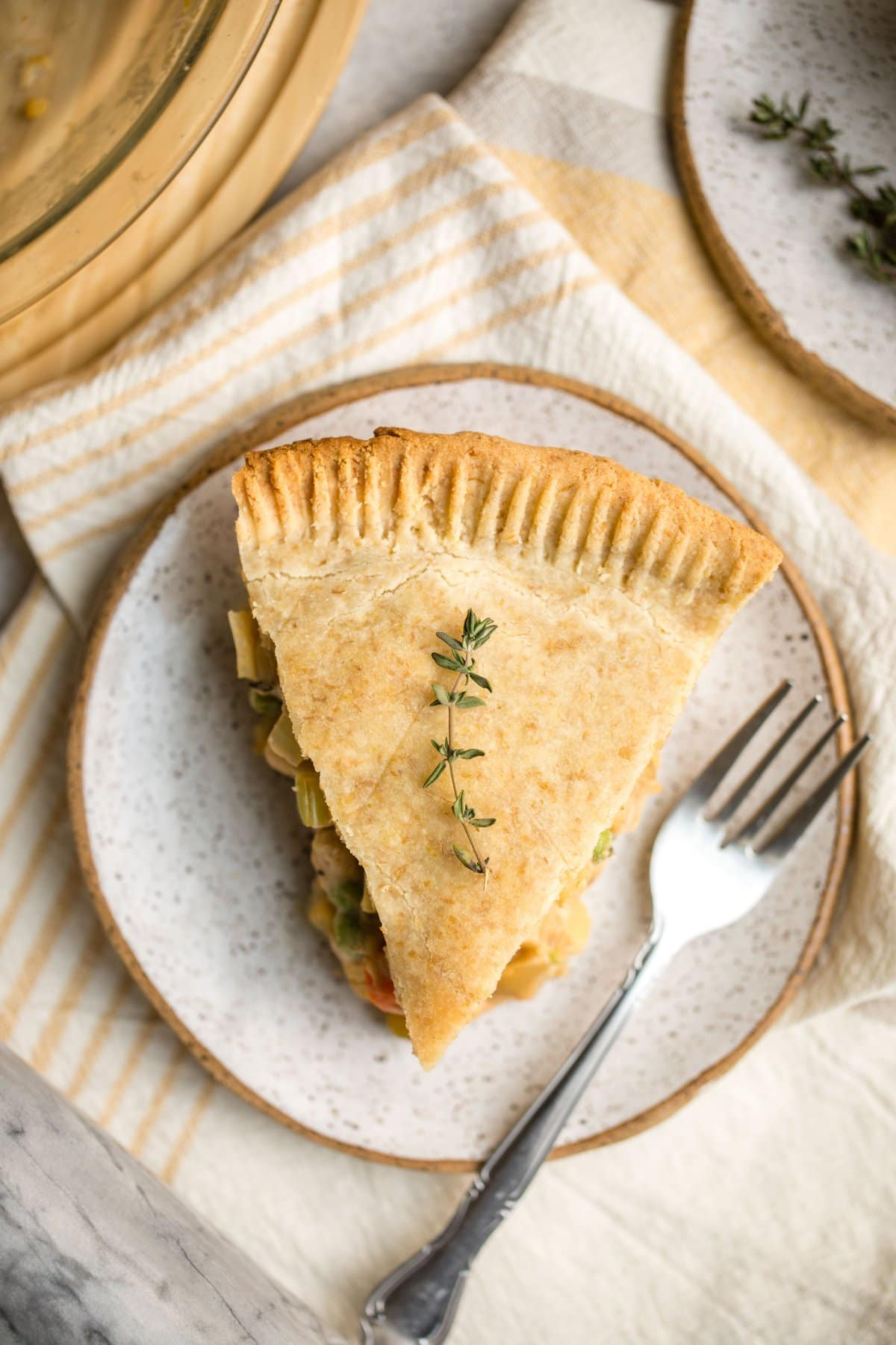 slice of chickpea pot pie topped with fresh thyme on white speckled plate