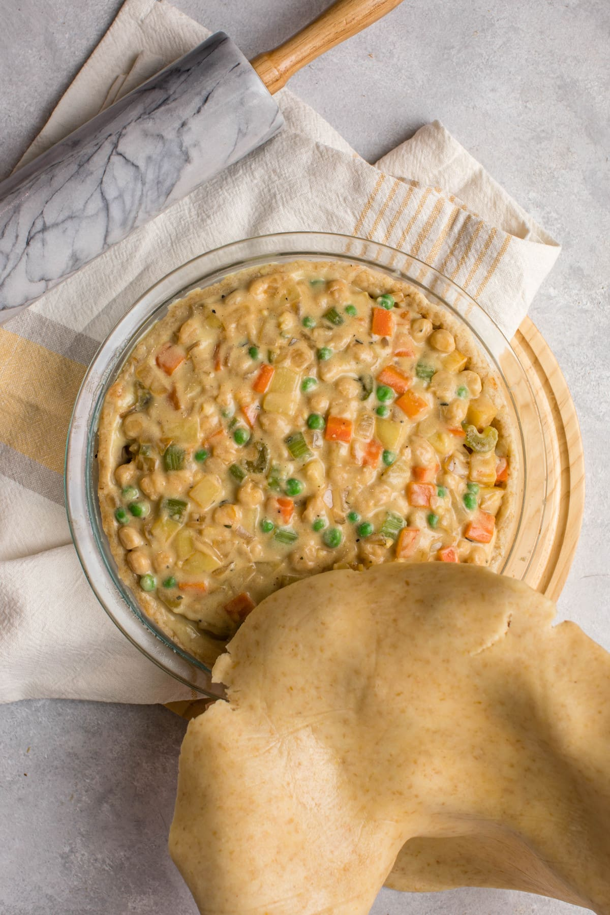 hands covering chickpea pot pie with uncooked top pie crust