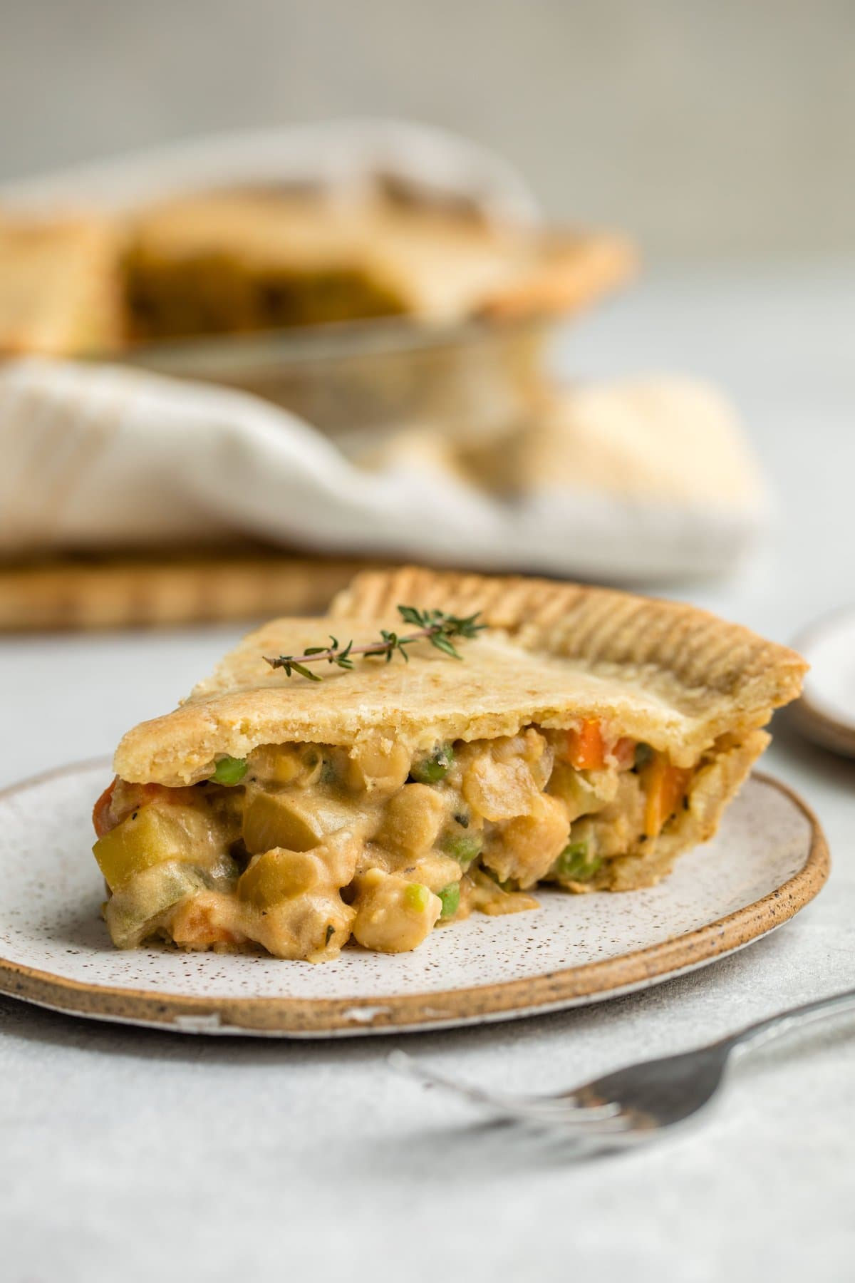 side view of slice of chickpea pot pie filled with chickpeas, peas and carrots on white speckled plate with silver fork