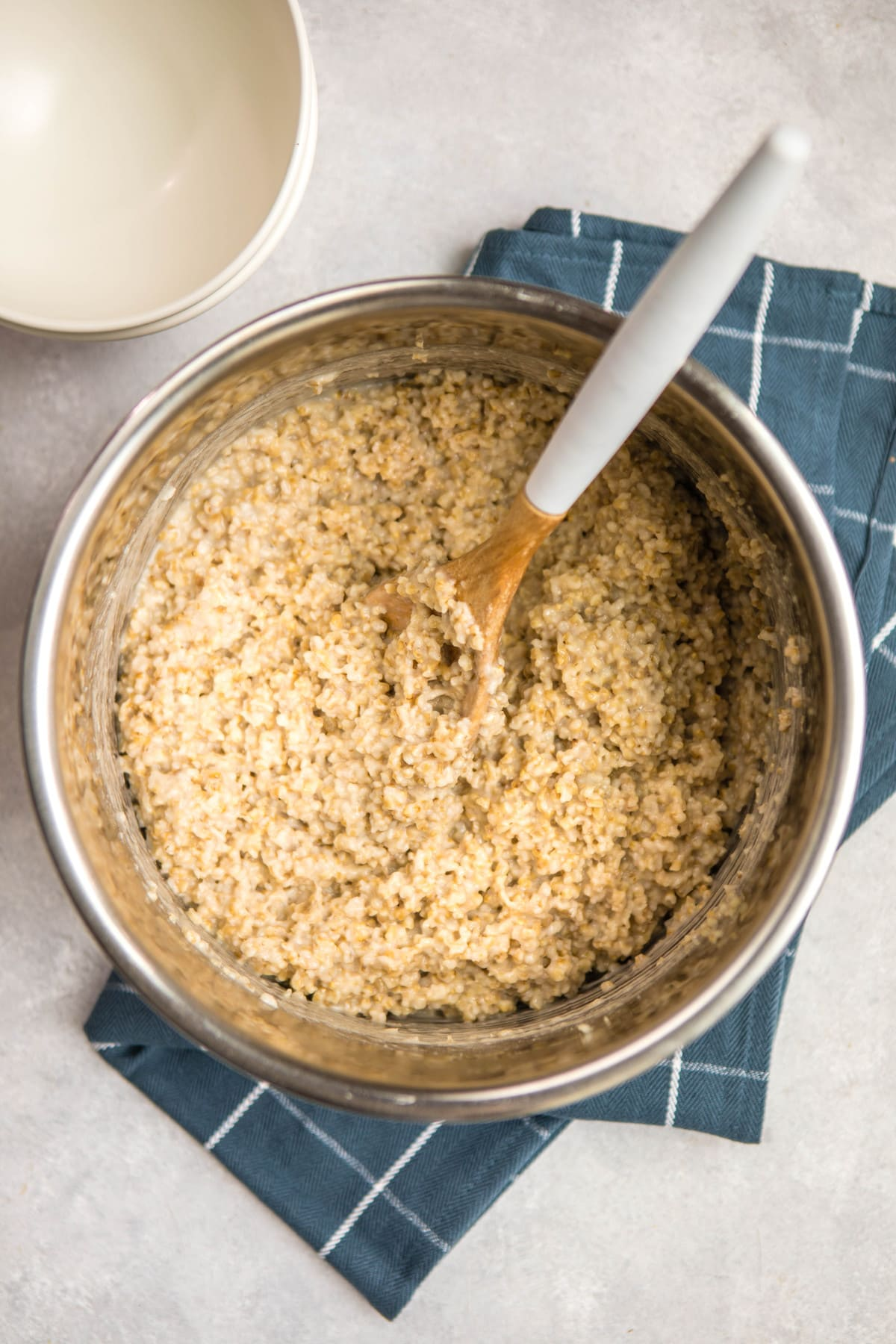 cooked steel cut oatmeal in instant pot with wooden spoon