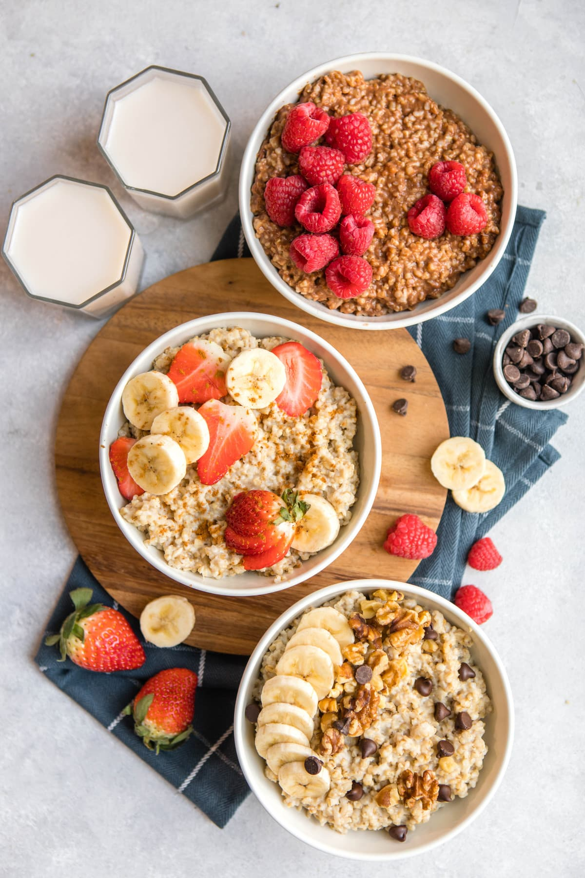 three white bowls of steel cut oatmeal topped with various toppings