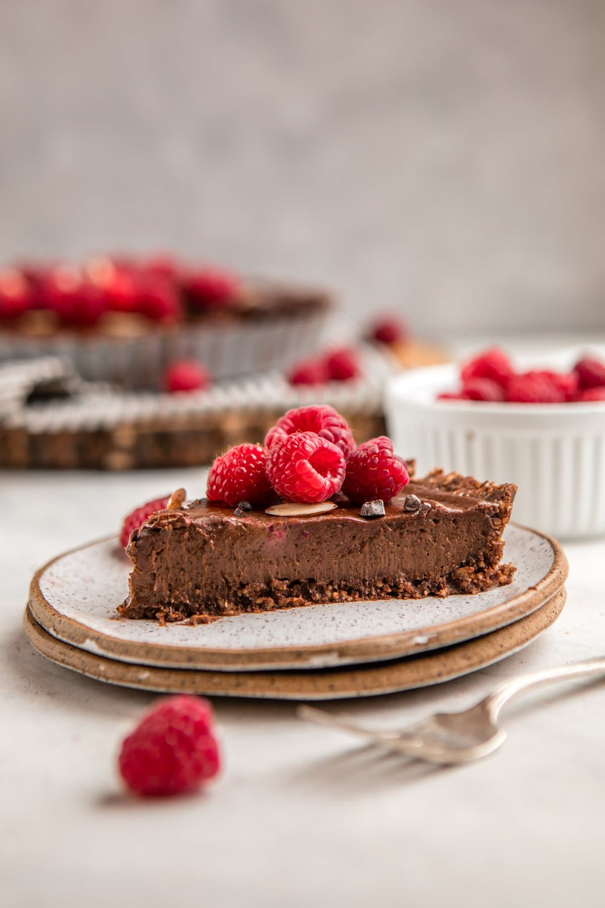slice of no bake chocolate raspberry tart on white speckled plate