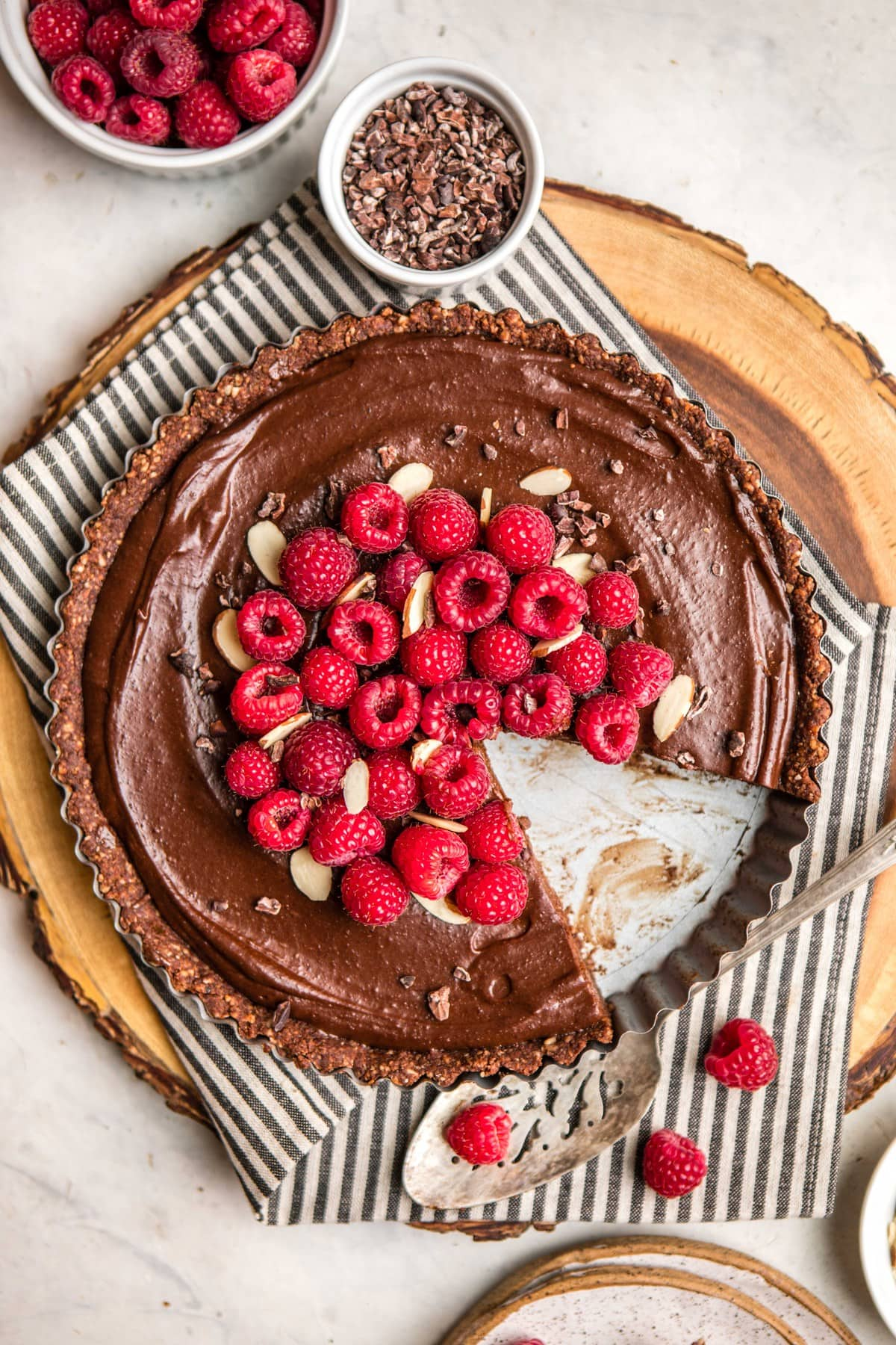 no bake chocolate raspberry ttart with slice taken out of it on wood serving tray