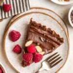 slice of no bake chocolate tart topped witth fresh raspberries and almonds