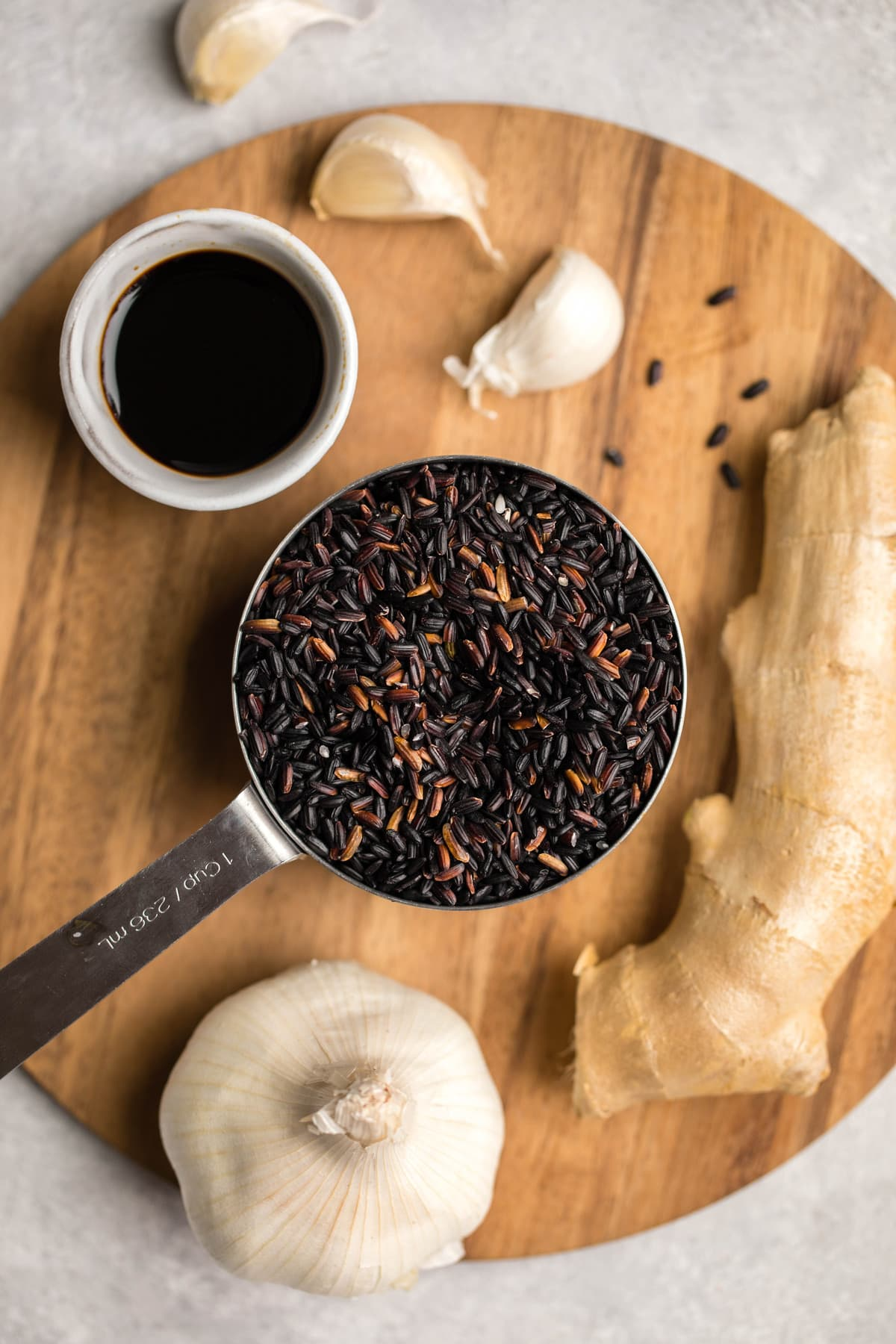 ingredients for teriyaki black rice arranged on round wooden cutting board