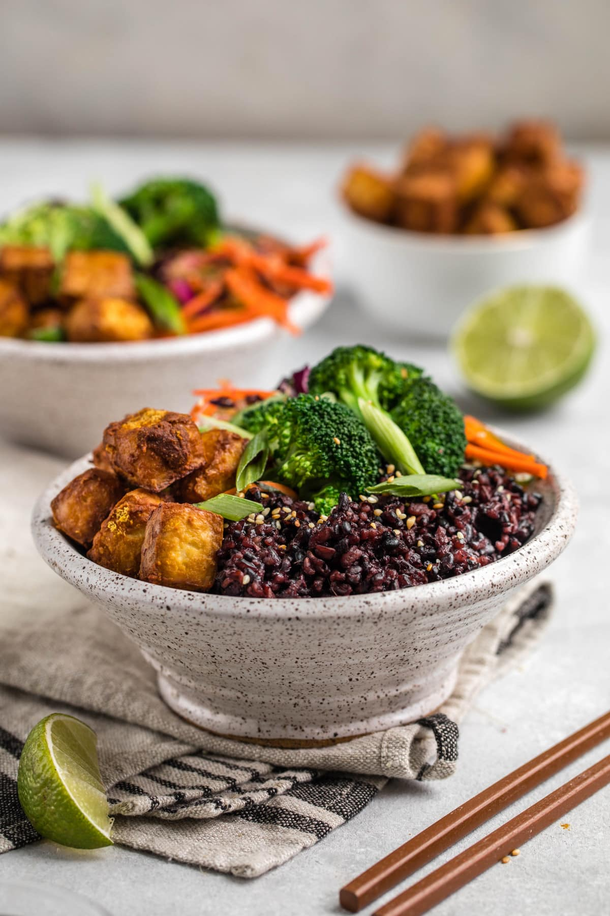 side view of two white speckled bowls filled with black rice, crispy tofu, broccoli, and asian slaw