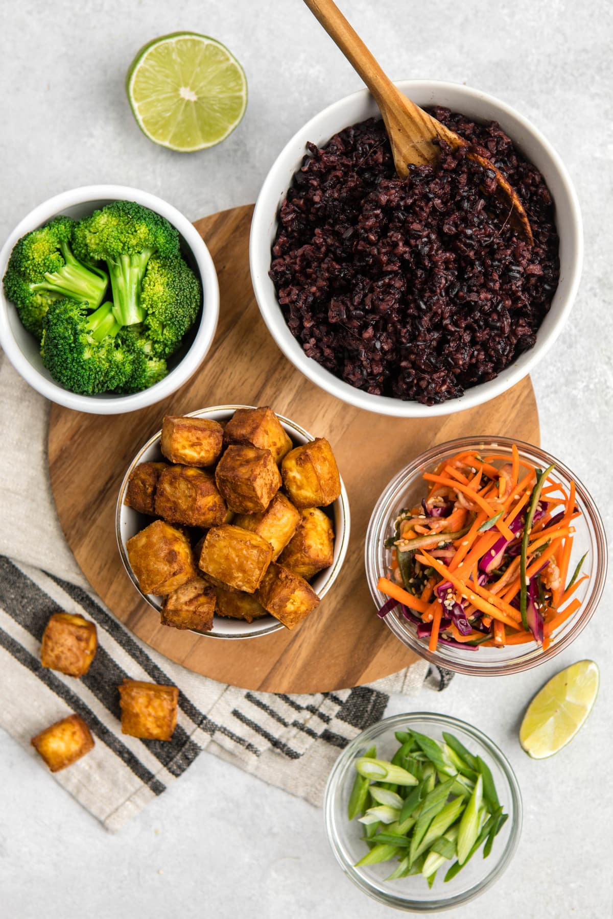 ingredients for black rice bowls in small glass bowls arranged on gray stone backdrop