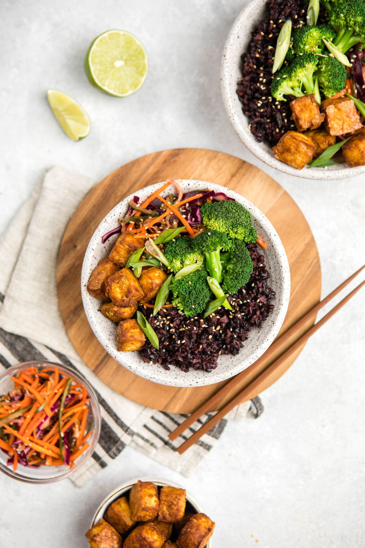 two bowls filled with black rice, tofu, and steamed broccoli and garnished with sesame seeds